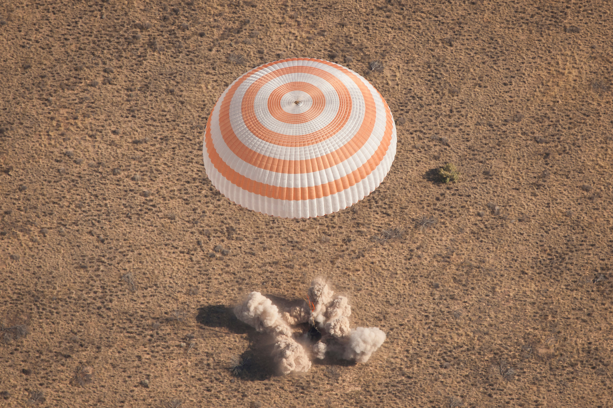 "A Soyuz lands with a parachute and last-second ""soft"" landing jets. Photo Credit: Bill Ingalls / NASA"