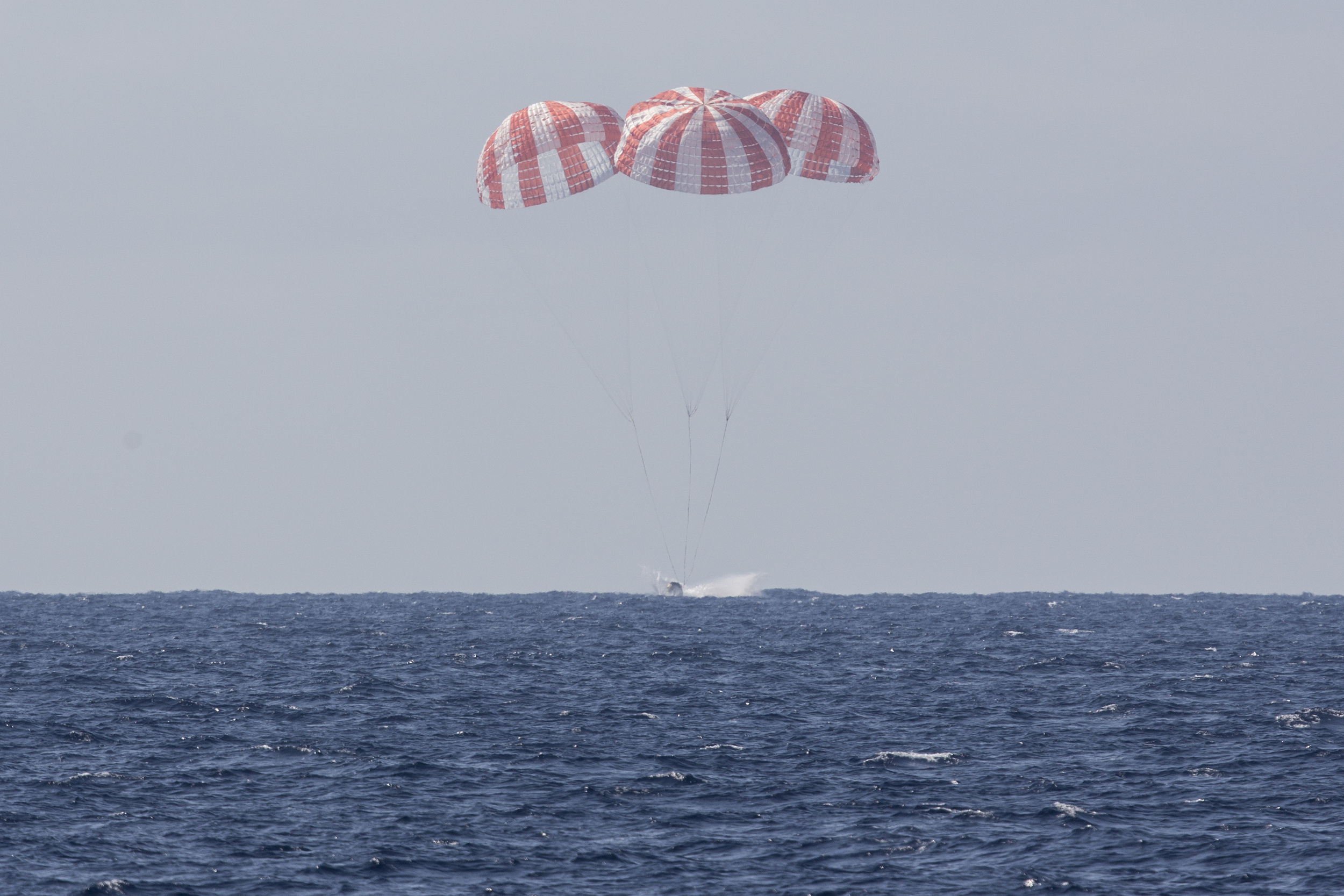Dragon parachutes into the Pacific Ocean after leaving the ISS. Photo Credit: SpaceX