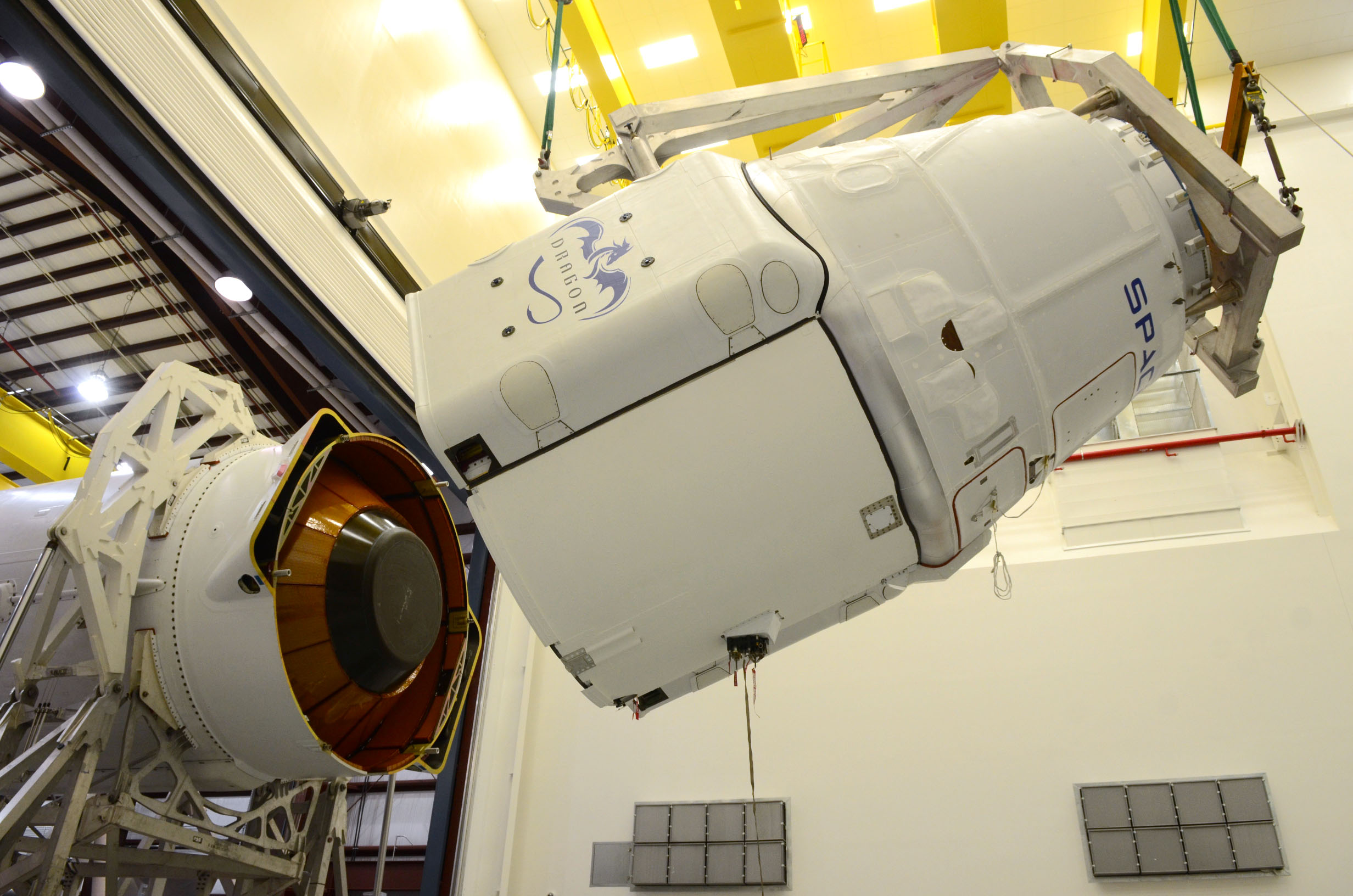 Engineers turn Dragon horizontal and attach it to the second stage of the Falcon 9 rocket. Photo Credit: SpaceX