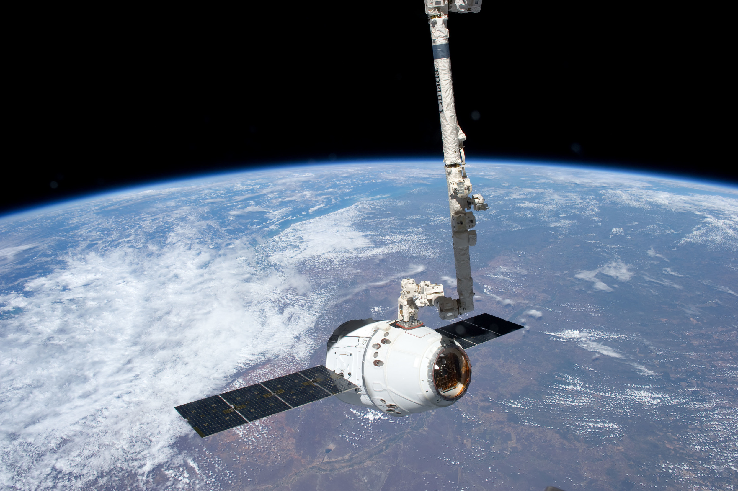 The crew of the ISS capture a Dragon with the robotic arm,  Canadarm2 . Photo Credit: NASA