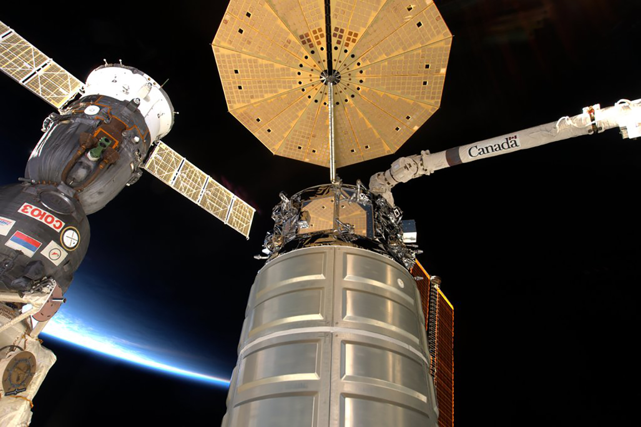 A Cygnus attached to the outpost with a Soyuz in the background. Photo Credit: NASA