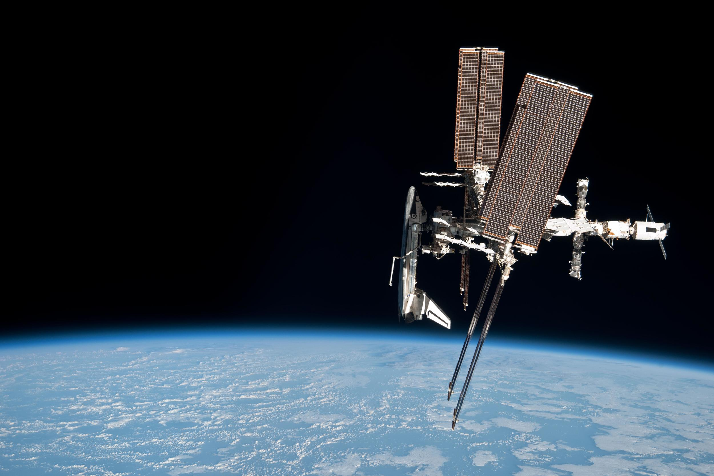 The space shuttle  Endeavour  is seen docked with the ISS by a departing Soyuz crew. Photo Credit: NASA