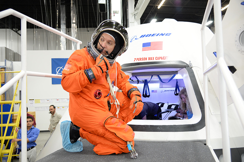 An astronaut practices entering the spacecraft in a flight suit. Photo Credit: Boeing