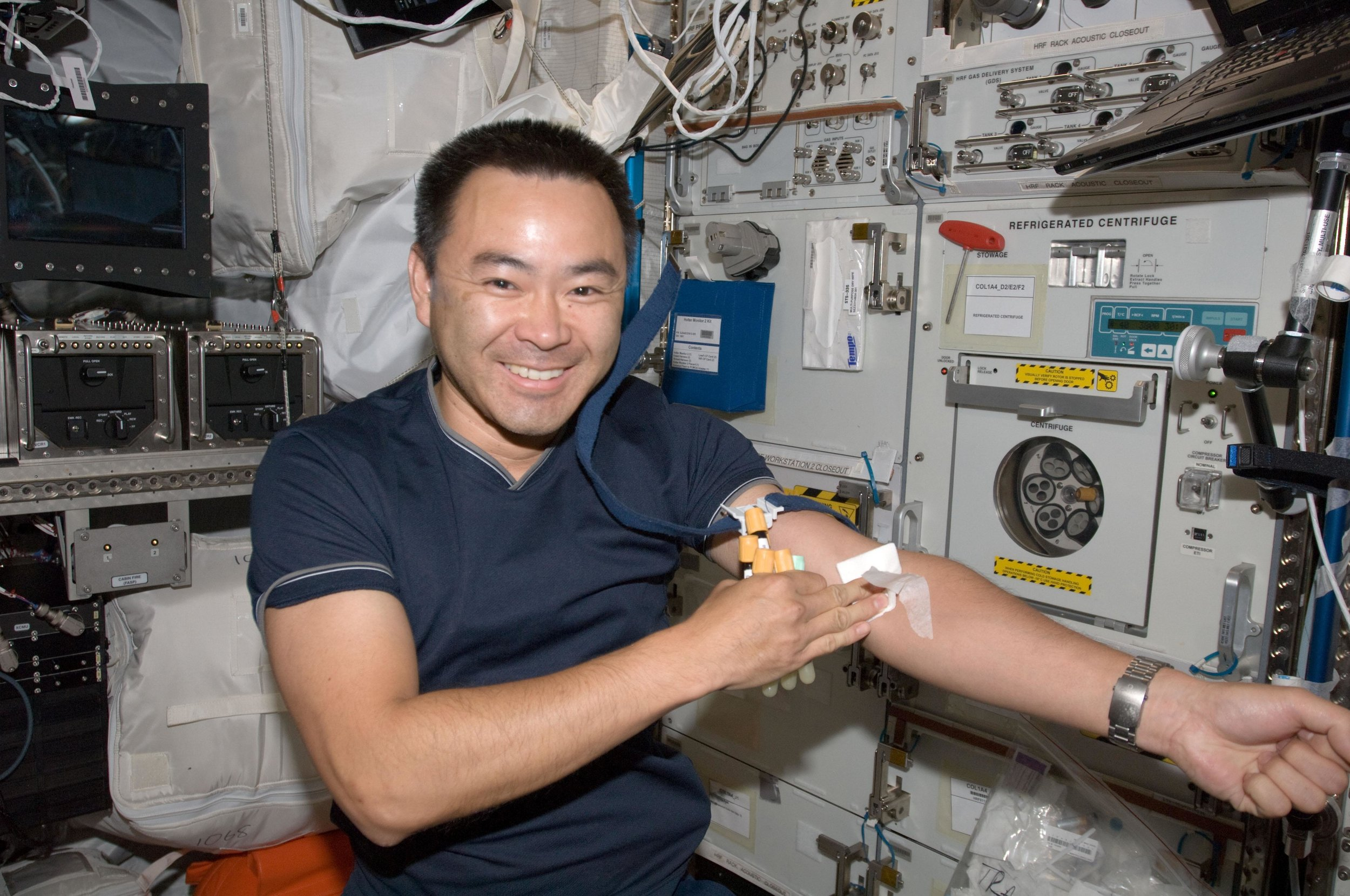 Japanese astronaut Akihiko Hoshide, a flight engineer for Expedition 32, places gauze on his harm after drawing blood for an immunological study. Photo Credit: NASA
