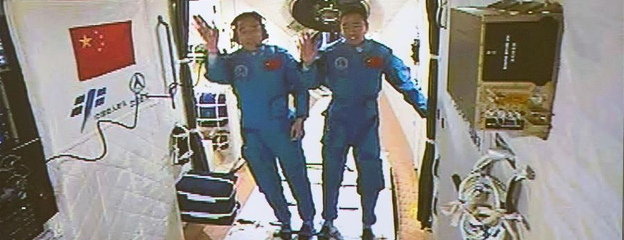 Jing Haipeng, left, and Chen Dong a few minutes after entering the Tiangong 2 space laboratory. Photo Credit: Xinhua