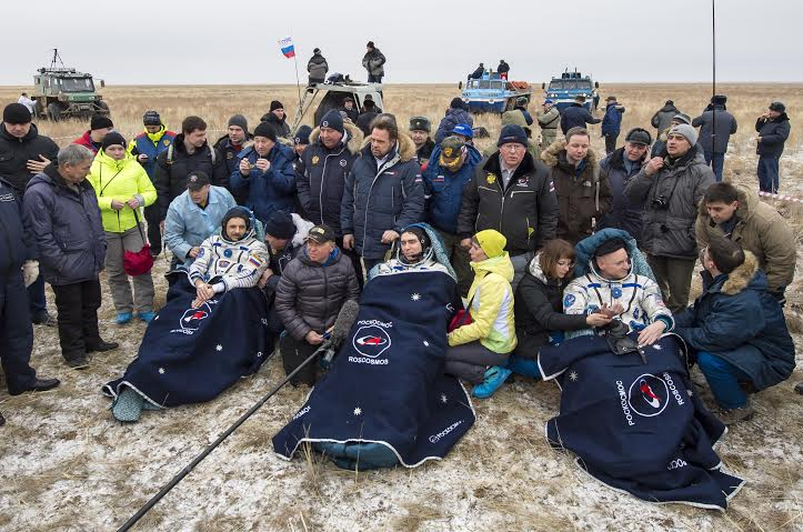Russian cosmonauts Mikhail Kornienko, left, Sergey Volkov of Roscosmos center, and Expedition 46 Commander Scott Kelly of NASA rest in chairs outside of the Soyuz TMA-18M spacecraft after they landed. Photo Credit: Bill Ingalls / NASA