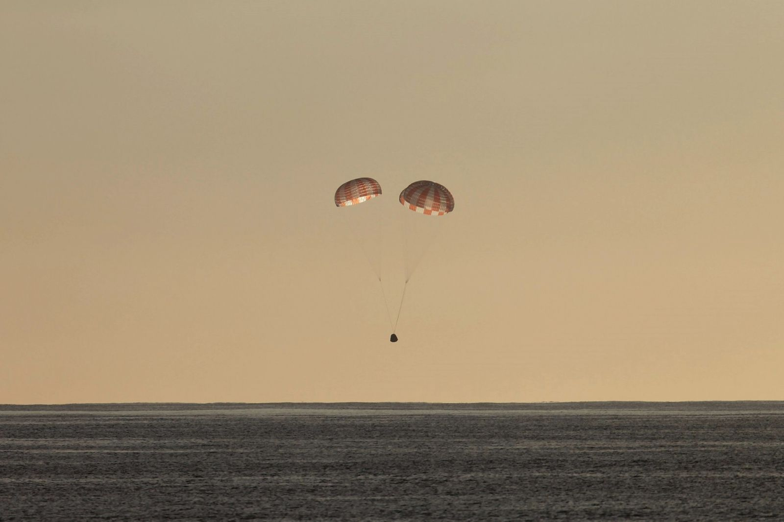 The SpaceX Dragon capsule is pictured seconds before splashing down in the Pacific Ocean. Photo Credit: SpaceX