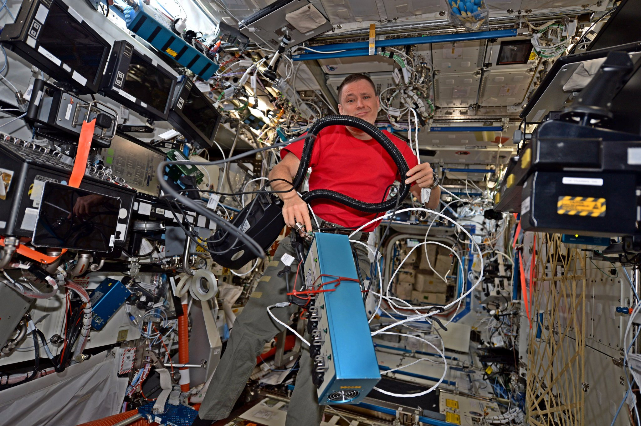 Astronaut Jack Fischer works to untangle cables and cords on the International Space Station. Photo Credit: NASA