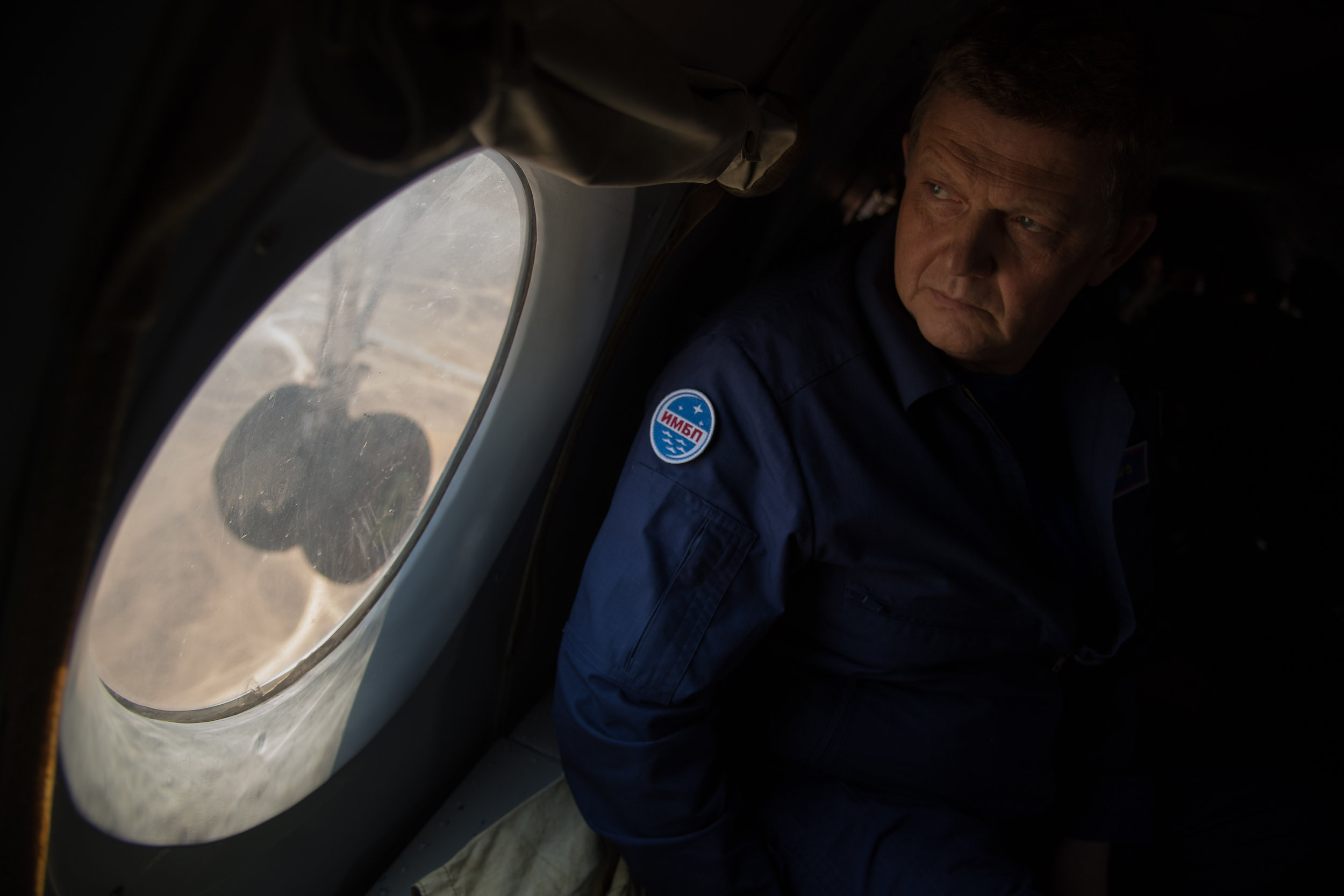 Director of the Russian Institute for Biomedical Problems (IMBP) Oleg Orlov looks out the window of an AN-26 aircraft as support teams pre-position to Zhezkazgan, Kazakhstan. Photo and Caption Credit: Bill Ingalls / NASA