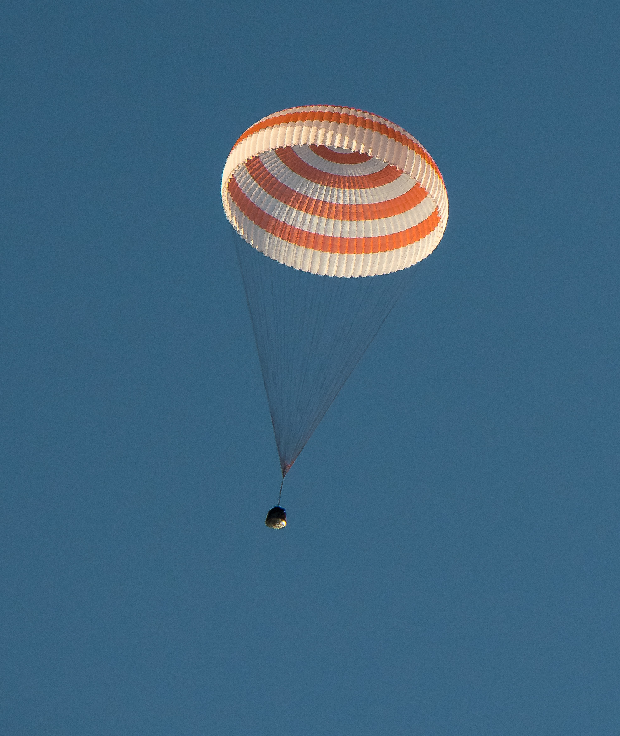 The Soyuz MS-04 capsule descends under its single main parachute. Photo Credit: Bill Ingalls / NASA