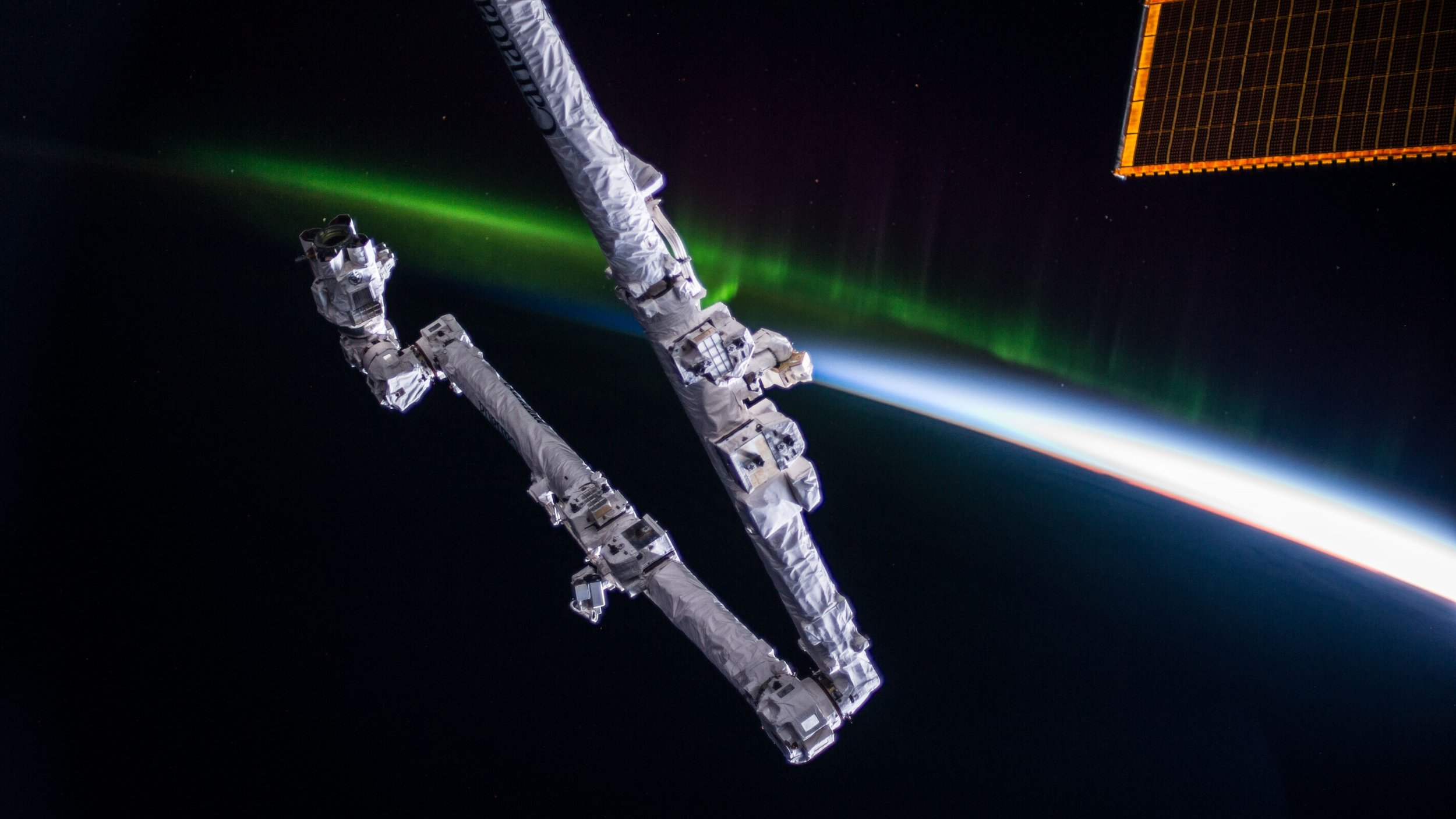 Canadarm2, the International Space Station's primary robotic arm, is seen attached to the outpost with an aurora in the background. Credit: NASA