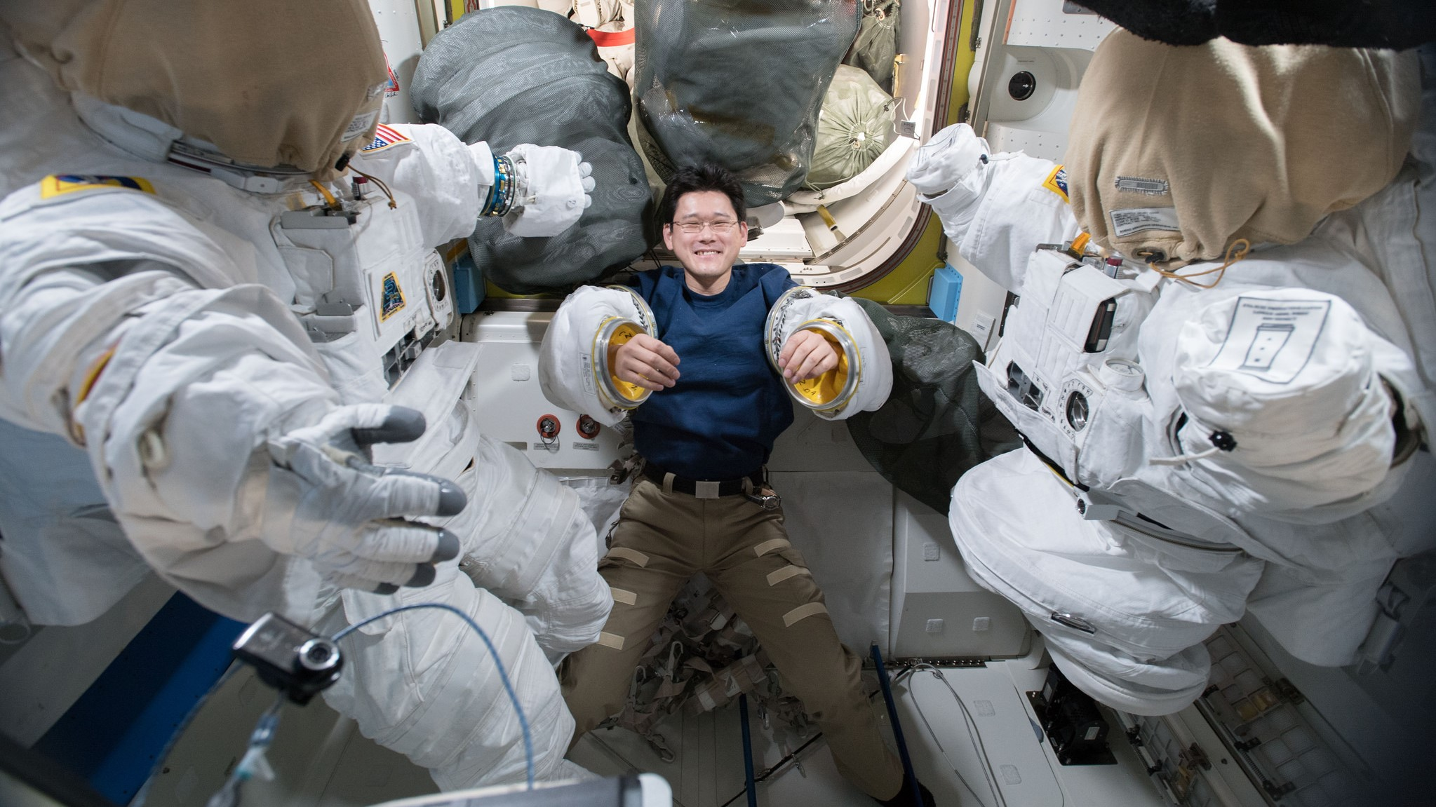 Japan Aerospace Exploration Agency astronaut Norishige Kanai tries on spacesuit sleeves inside the Quest airlock in preparation for the eventual U.S. EVA-48.Credit: NASA