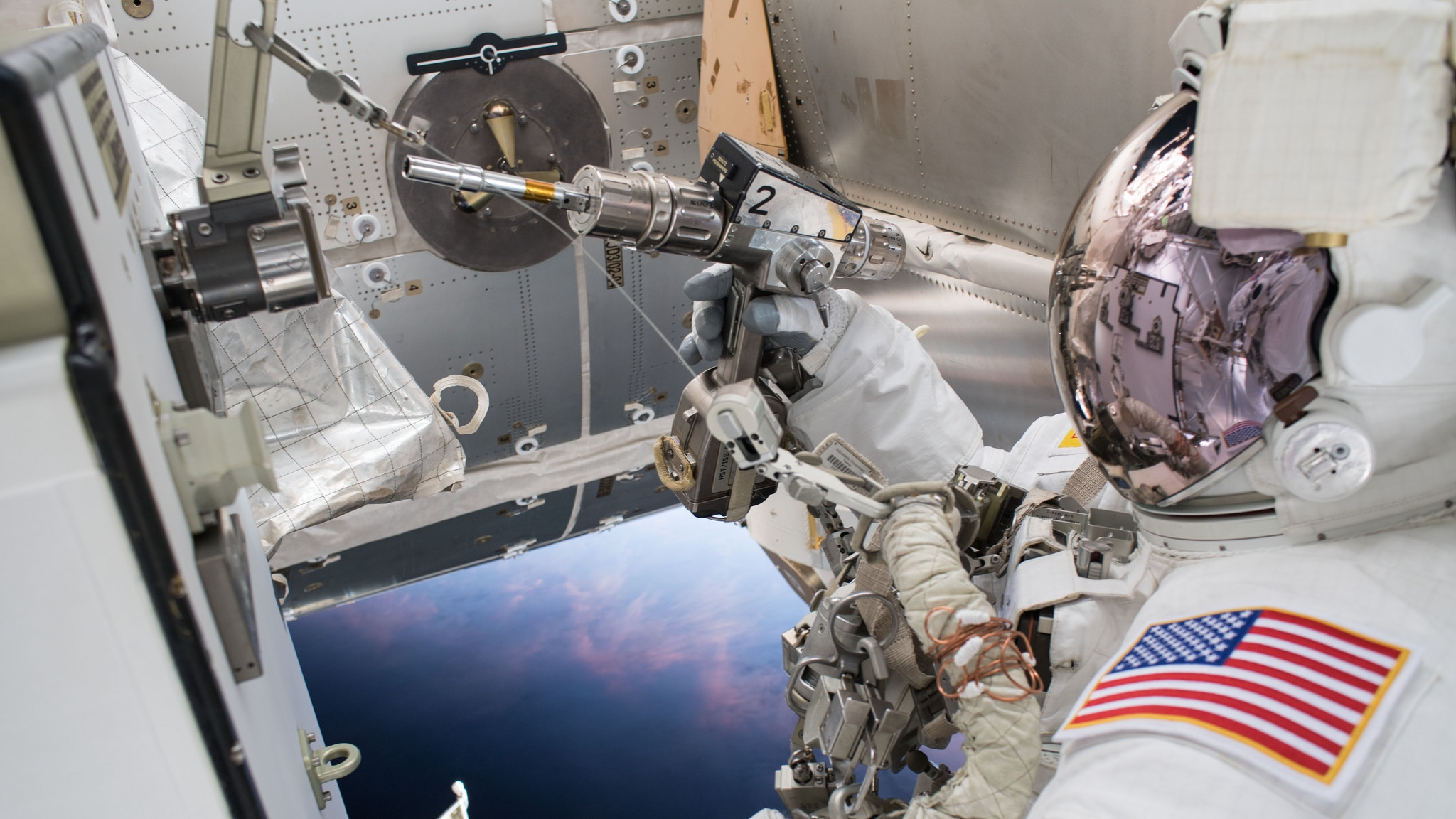 NASA's Drew Feustel works to swap a coolant pump. Credit: NASA