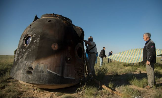 Russian search and rescue teams work to extract the crew from the capsule. Credit: Bill Ingalls / NASA