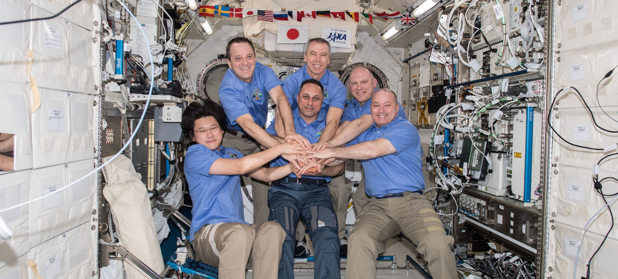The six-person Expedition 55 crew pose for a portrait inside the Japanese Kibo laboratory. ISS Commander Anton Shkaplerov is in the center. From left to right around him are Norishige Kanai, Ricky Arnold, Drew Feustel, Oleg Artemyev and Scott Tingle. Credit: NASA