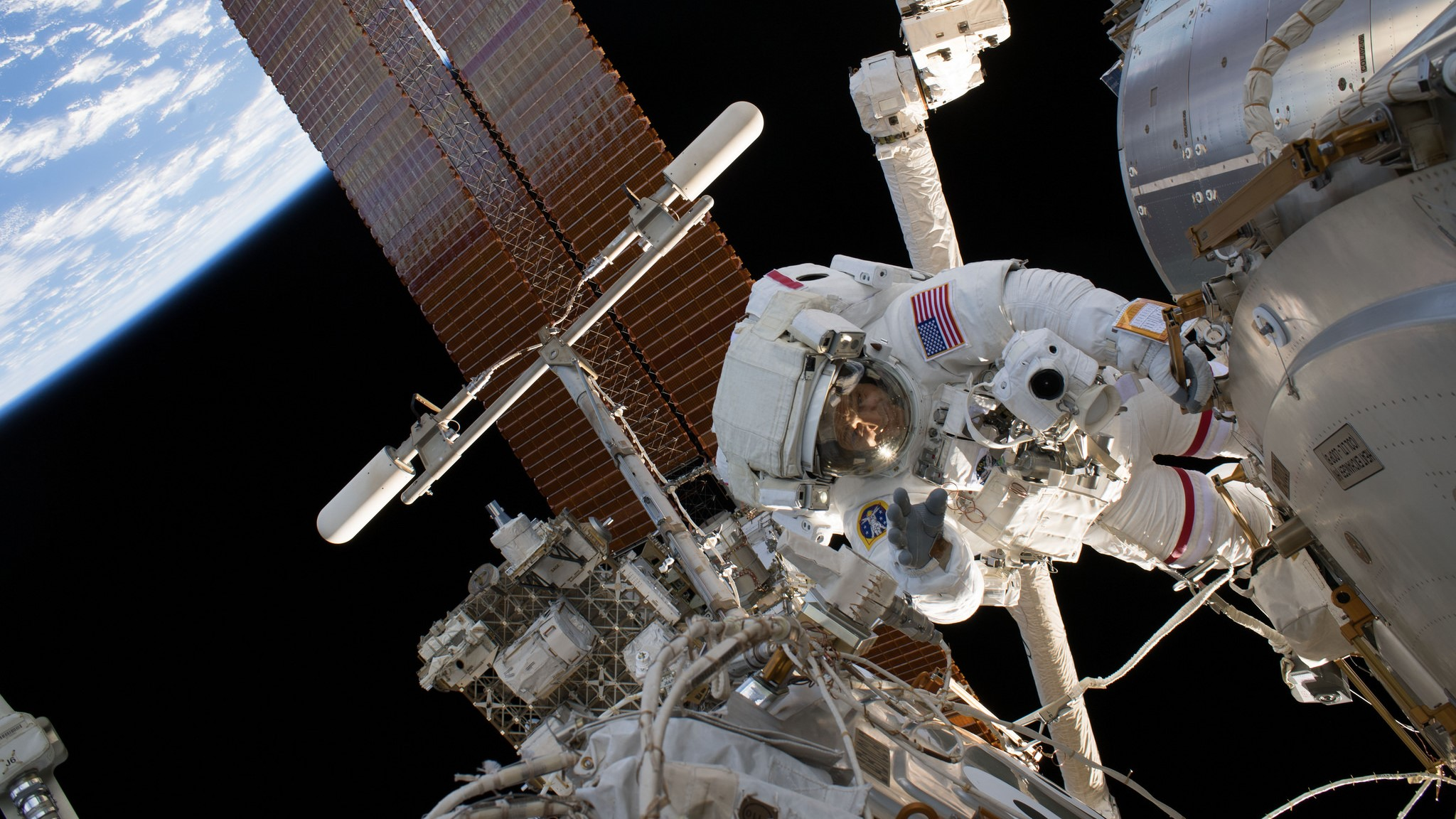 """NASA astronaut Ricky Arnold, the lead spacewalker for U.S. EVA-51, works outside the International Space Station with NASA's Drew Feustel, not pictured, to install several high-definition cameras to provide """"enhanced views"""" of the upcoming commercial crew flights by SpaceX and Boeing. Credit: NASA"""