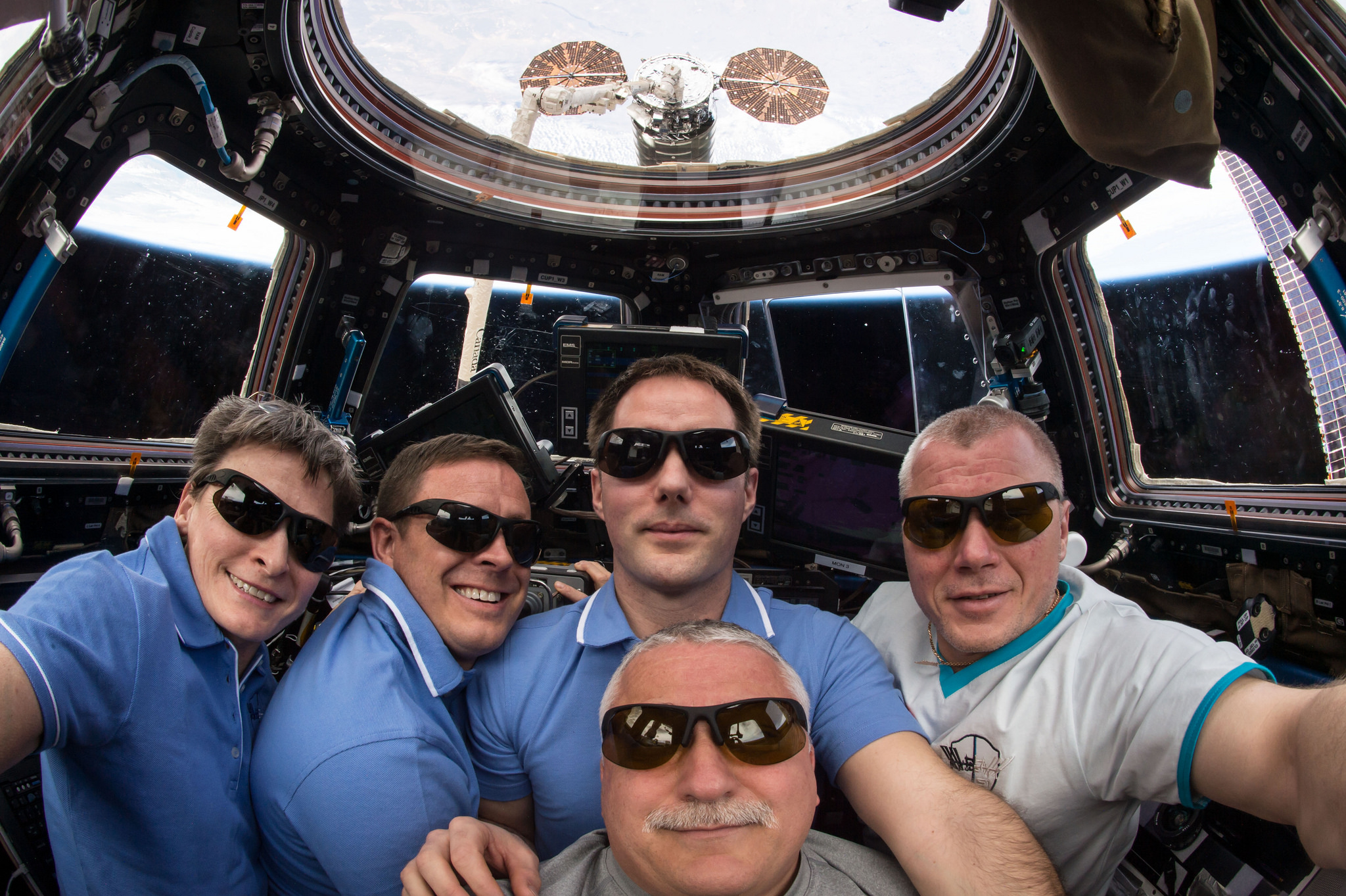 The Expedition 51 crew pose in for a group photo in the cupola window not long after the capture of the OA-7 Cygnus spacecraft. Credit: NASA