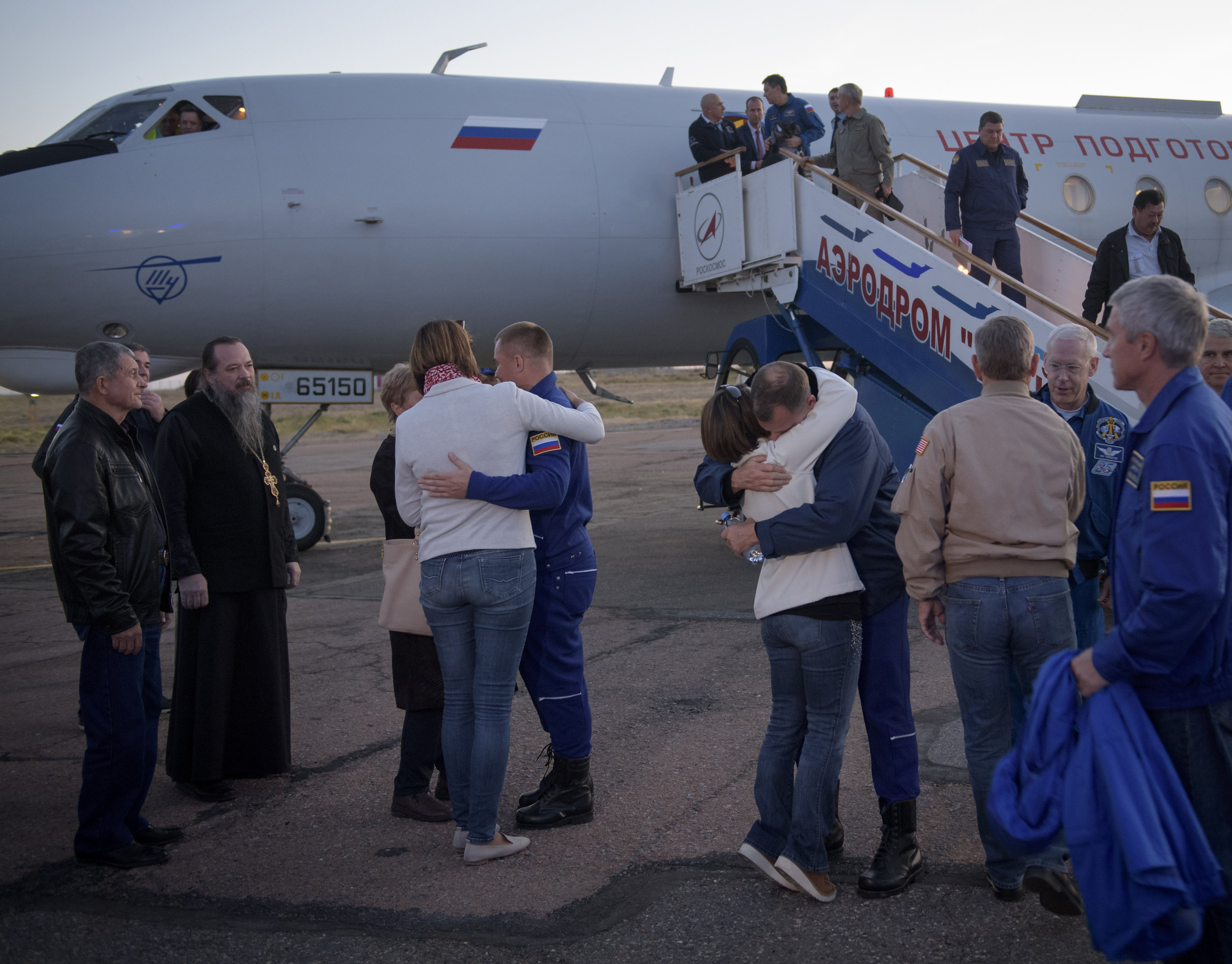 Alexsey Ovchinin, left and Nick Hague embrace their families after landing at the airport in Baikonur following their in-flight abort. Credit: NASA/Bill Ingalls