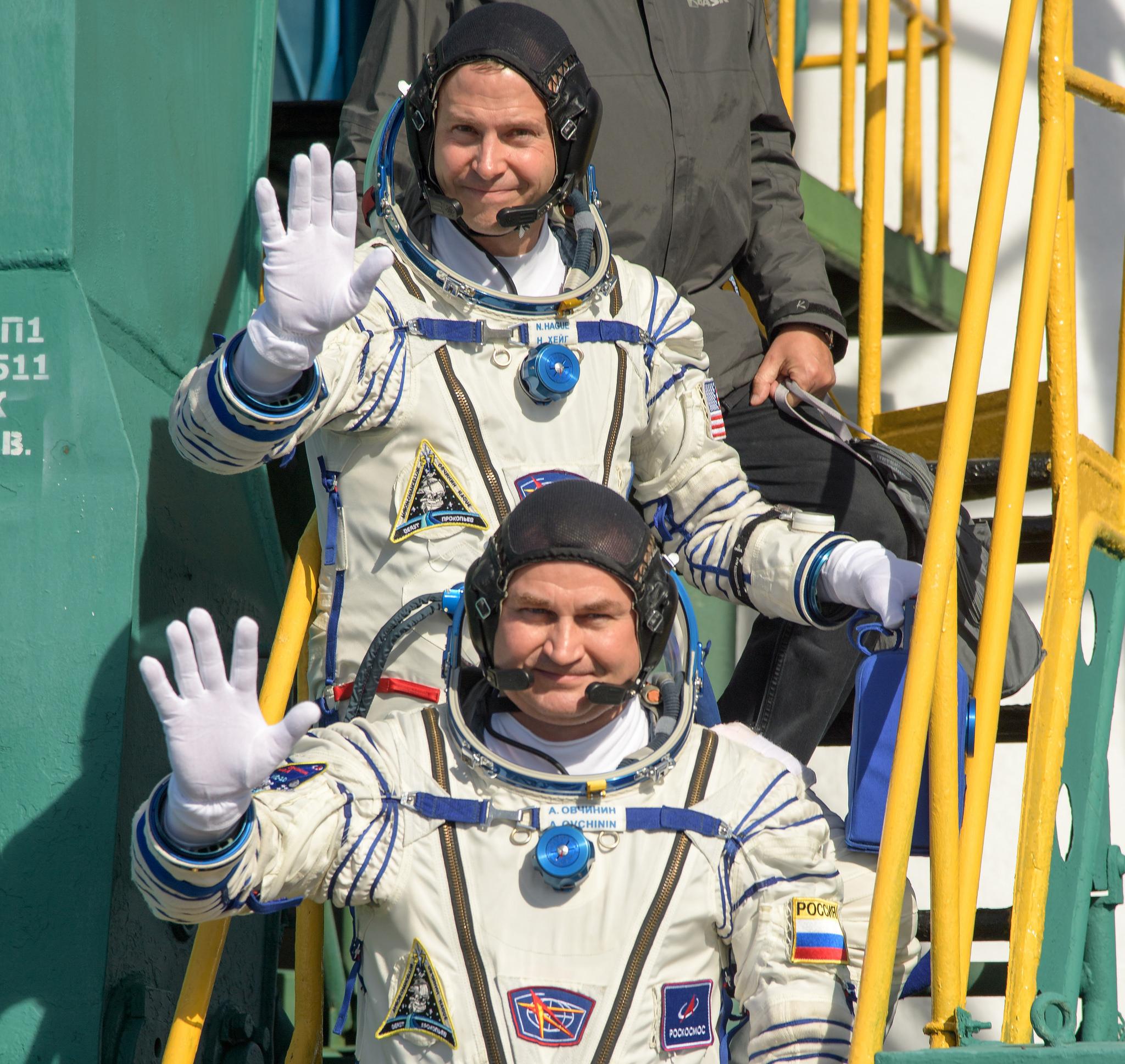 NASA astronaut Nick Hague, top, and Russian cosmonaut Alexsey Ovchinin wave farewell before boarding their Soyuz spacecraft. Credit: NASA/Bill Ingalls