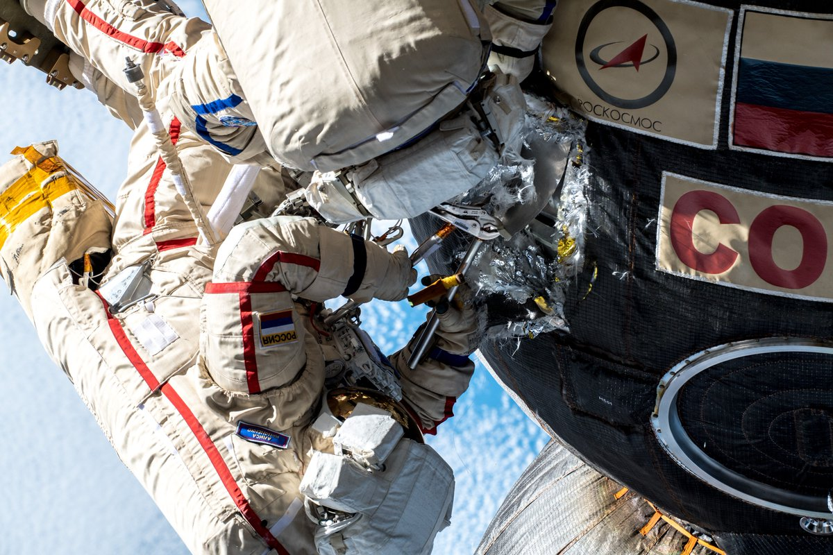 Russian cosmonauts Sergey Prokopyev and Oleg Kononenko work to remove thermal insulation and part of a micrometeoroid shield to get to the outer hull of the Soyuz to inspect a microcrack that was repaired from the inside several months before the spacewalk. Credit: Roscosmos
