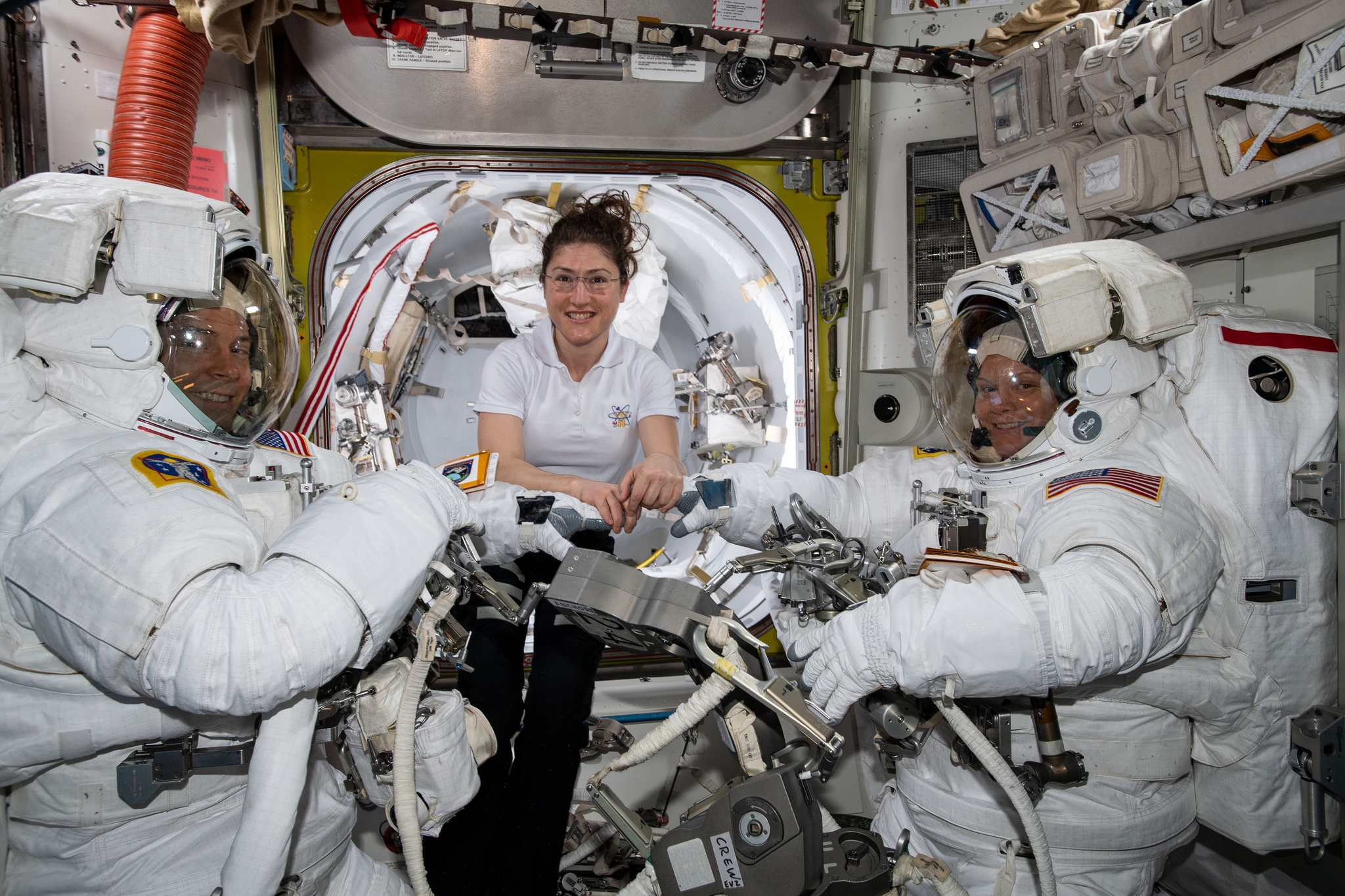 Nick Hague, left, and Anne McClain, right, are assisted in their spacesuits by Christina Koch for their March 22, 2019, spacewalk. Credit: NASA