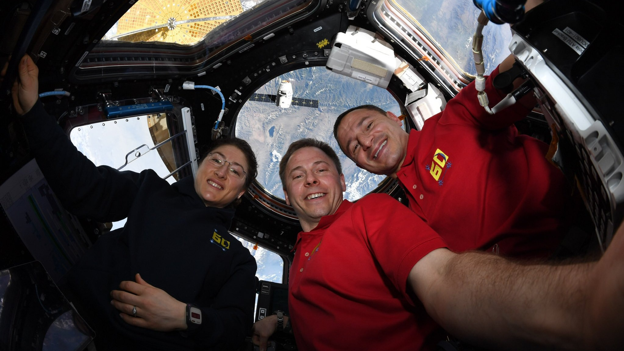 NASA astronauts Christina Koch, left, and Nick Hague, center, as well as European Space Agency astronaut Luca Parmitano, in the Cupola window with CRS-18 Dragon approaching beneath the space station. Credit: NASA