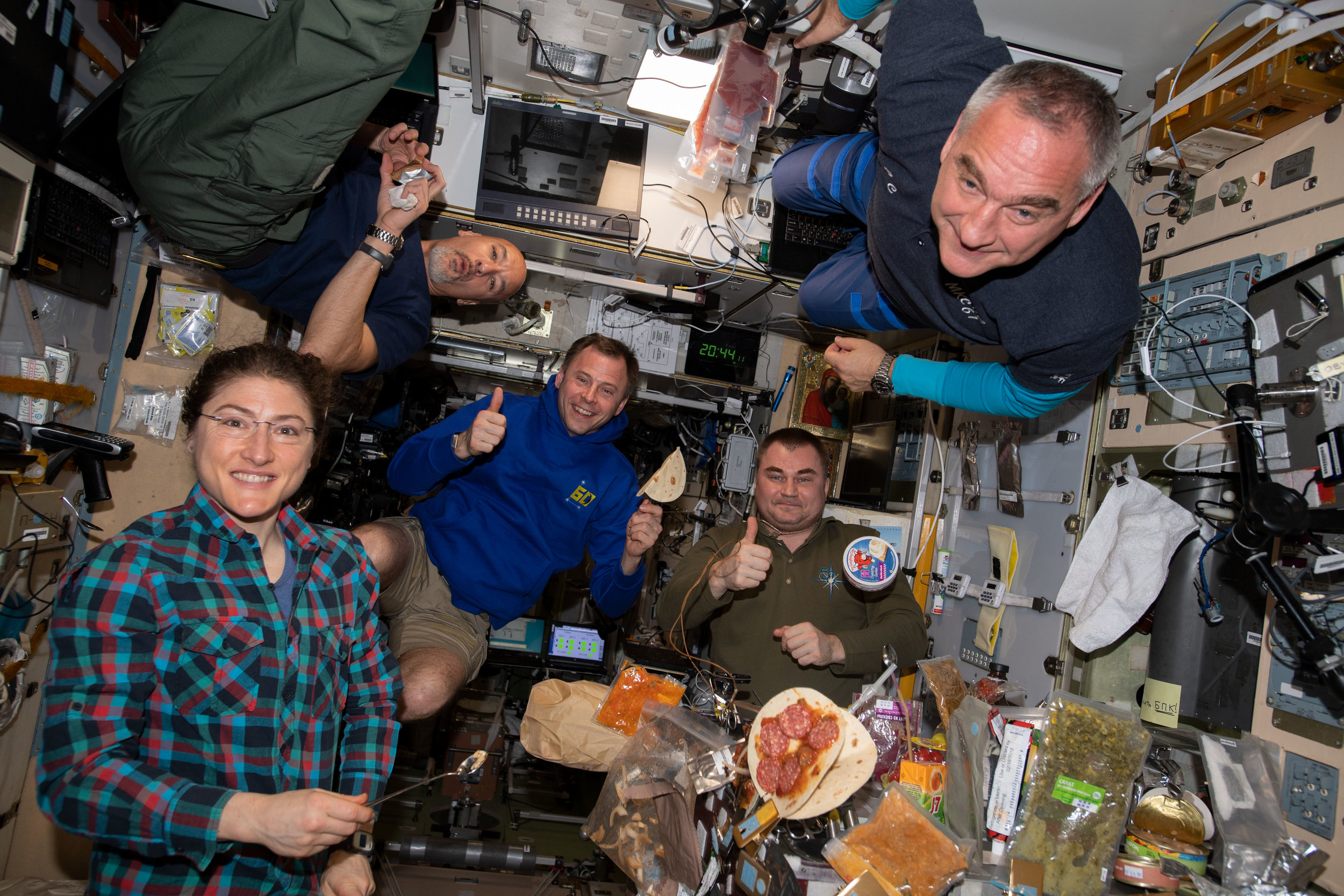 The Expedition 60 crew eats dinner together in the Zvezda module. From left are astronauts Christina Koch, Luca Parmitano and Nick Hague with cosmonauts Alexey Ovchinin and Alexander Skvortsov. Not pictured is astronaut Drew Morgan. Credit: NASA