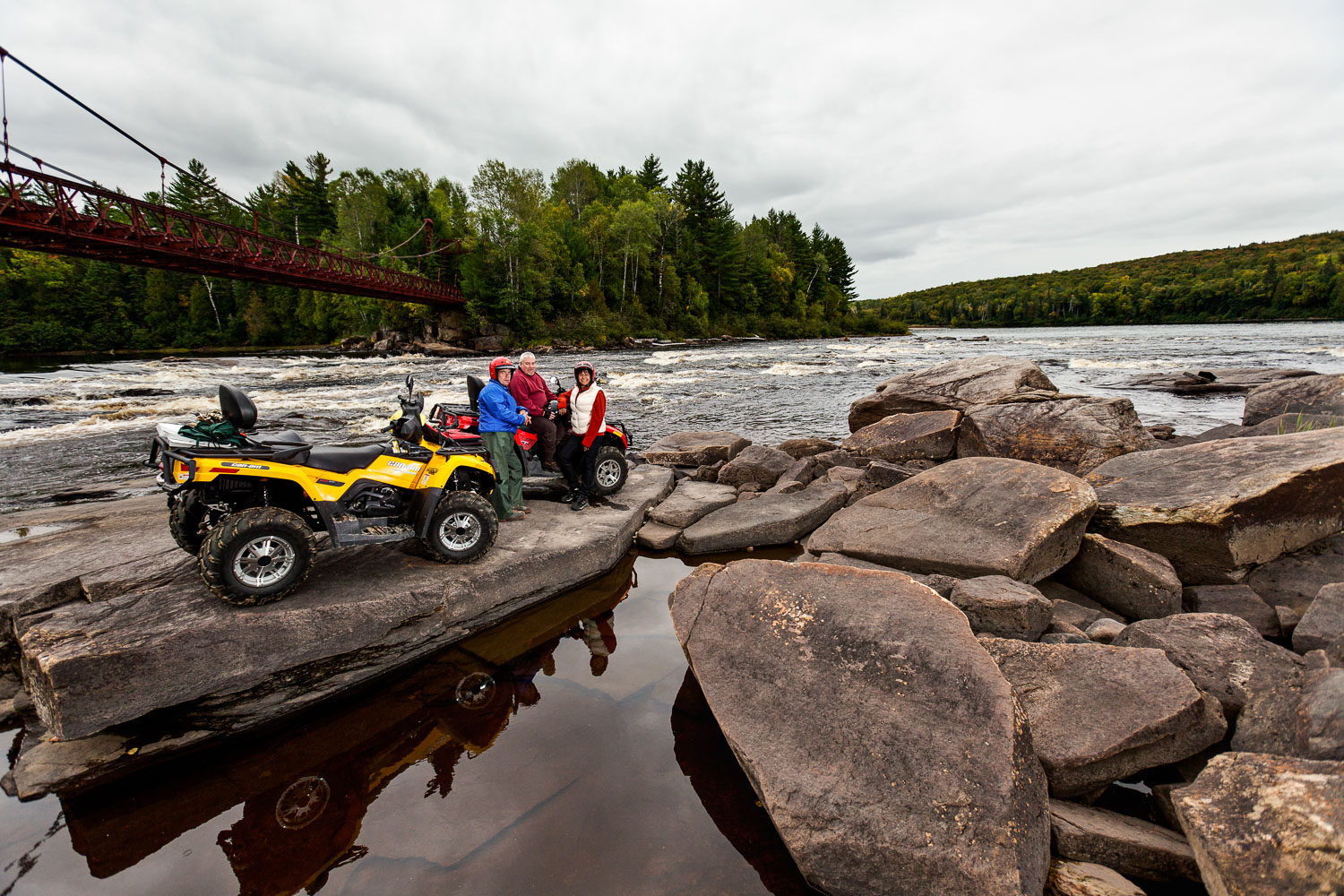 Photograph of some ATVs and their riders on a river