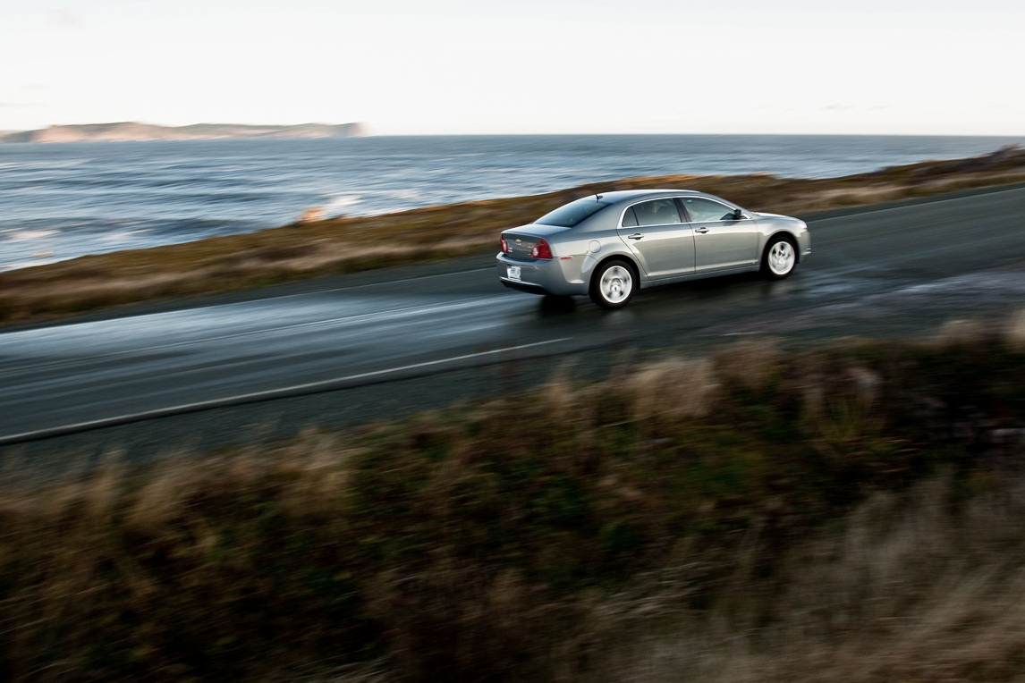 Photograph of a car on an ocean highway