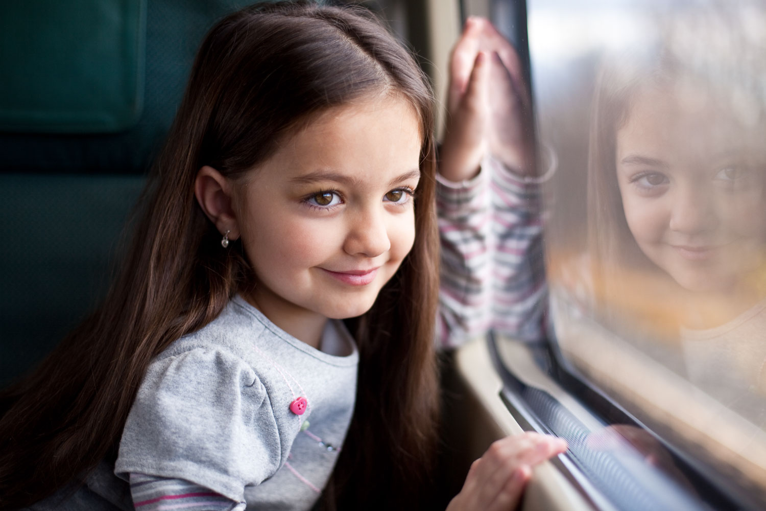 Portrait of a young girl looking out a train window