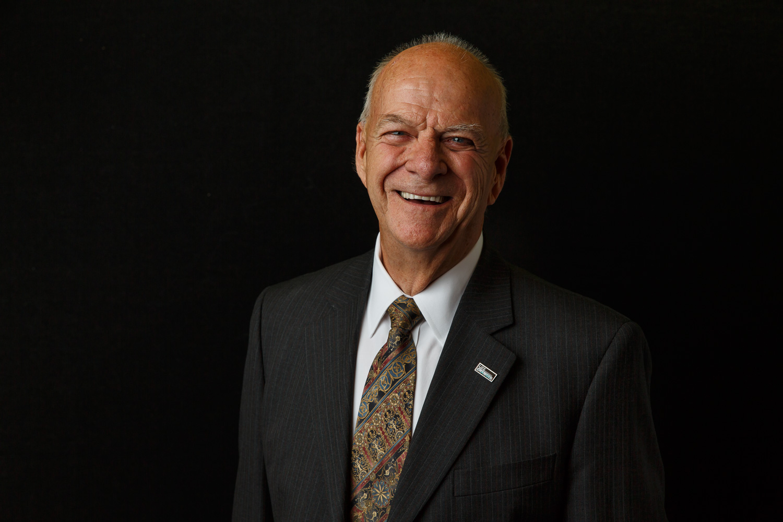 Headshot of a balding man on a black backdrop