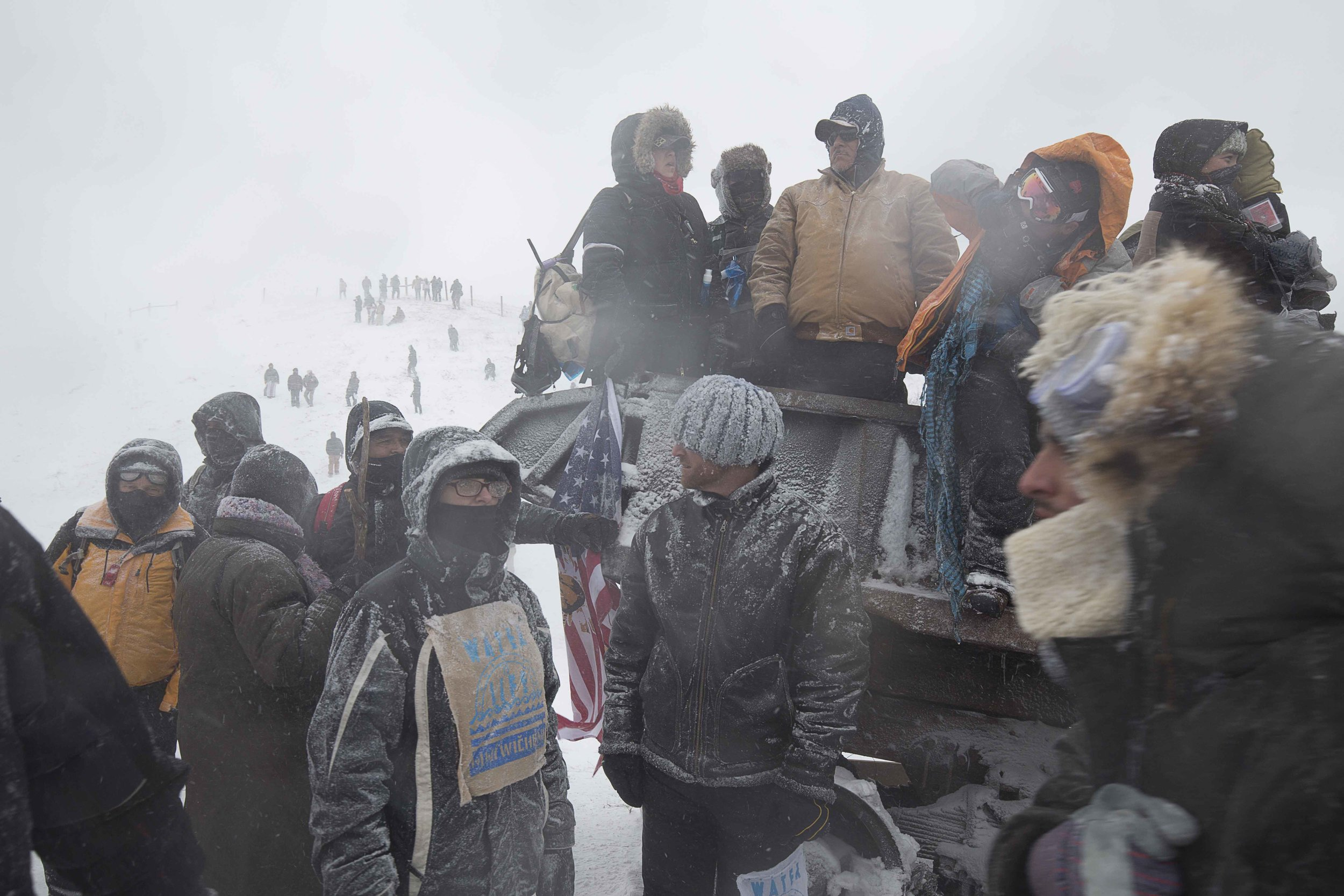 """Water Protectors and veterans from Oceti Sakowin protest camp gather along highway 1806 on December 5, 2016 during an """"unsanctioned"""" protest action, spurred by veterans who arrived the day before."""