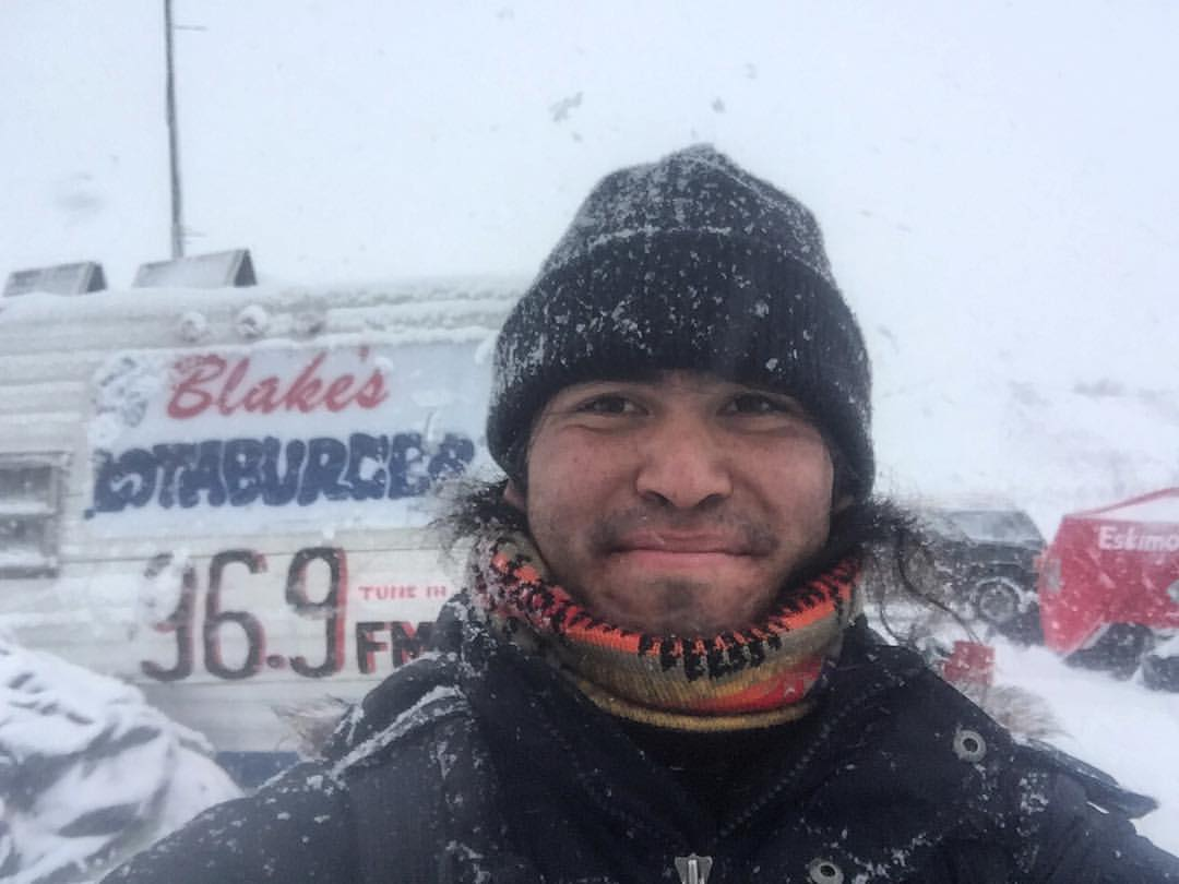 """I pose in front of a Navajo pirate radio station before the veteran protest, smiling with glee because of the """"Blake's Lotaburger"""" sign from Albuquerque, New Mexico."""