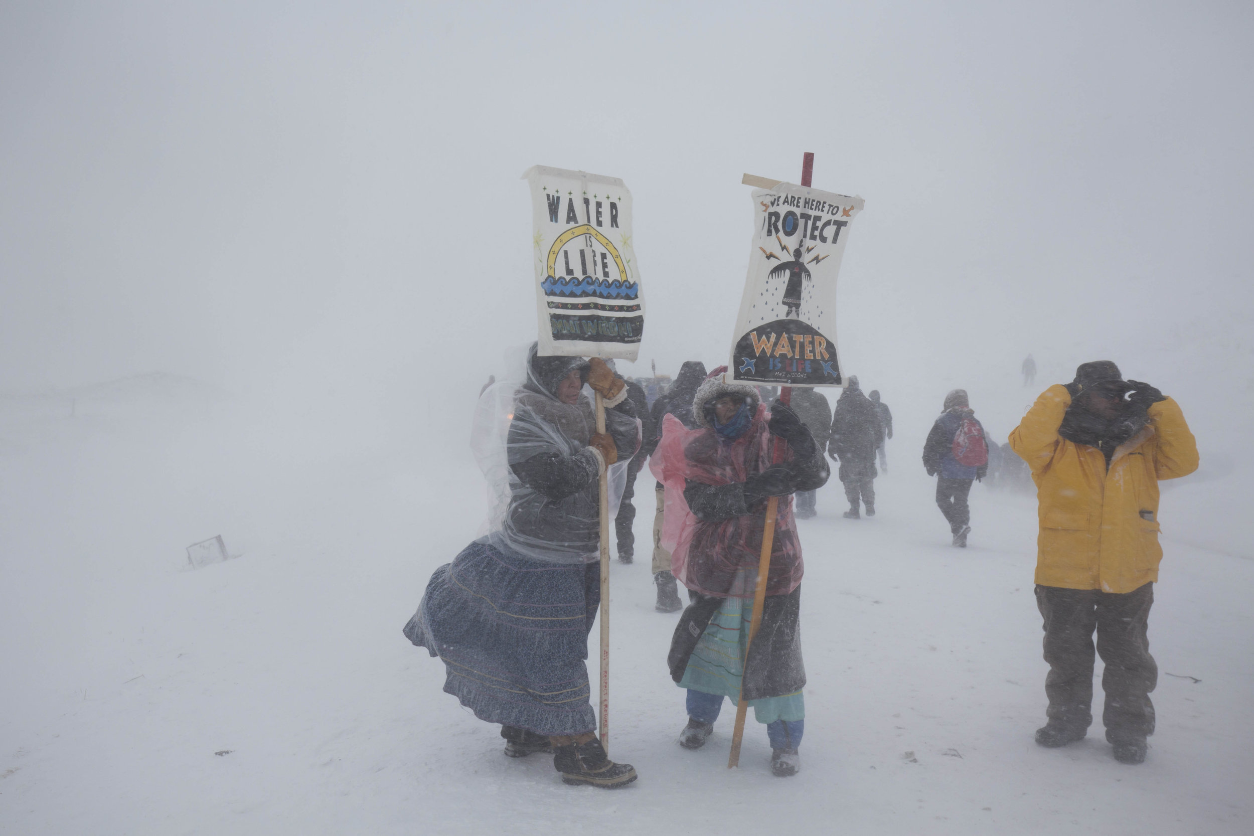 Two Water Protectors carry signs along highway 1806 on December 5, 2016, not far from Backwater Bridge where law enforcement and National Guard have blockaded.