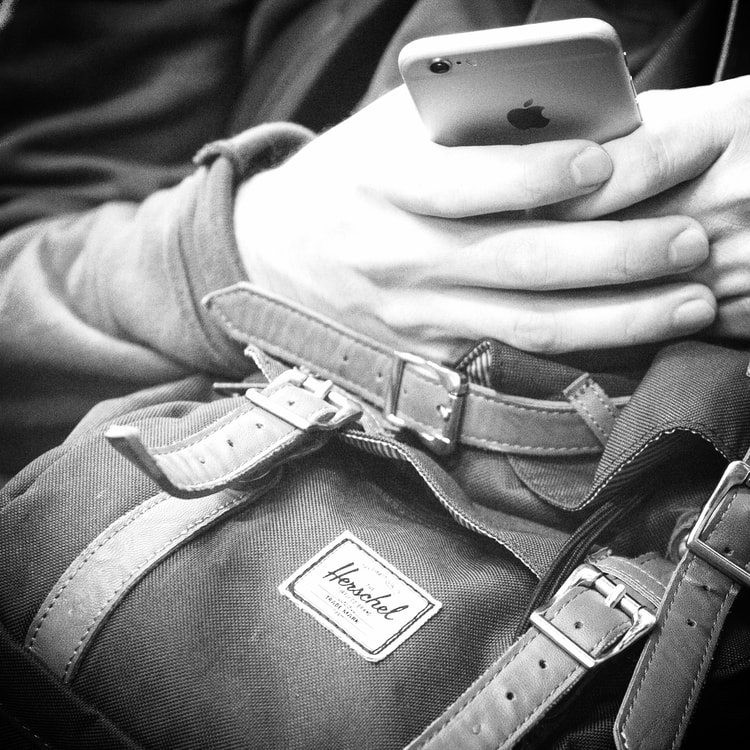 man on iphone - commuting to work