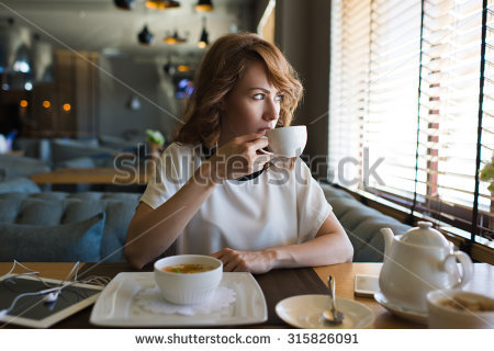 stock-photo-portrait-of-young-gorgeous-female-drinking-tea-while-looking-out-of-the-coffee-shop-window-and-315826091.jpg