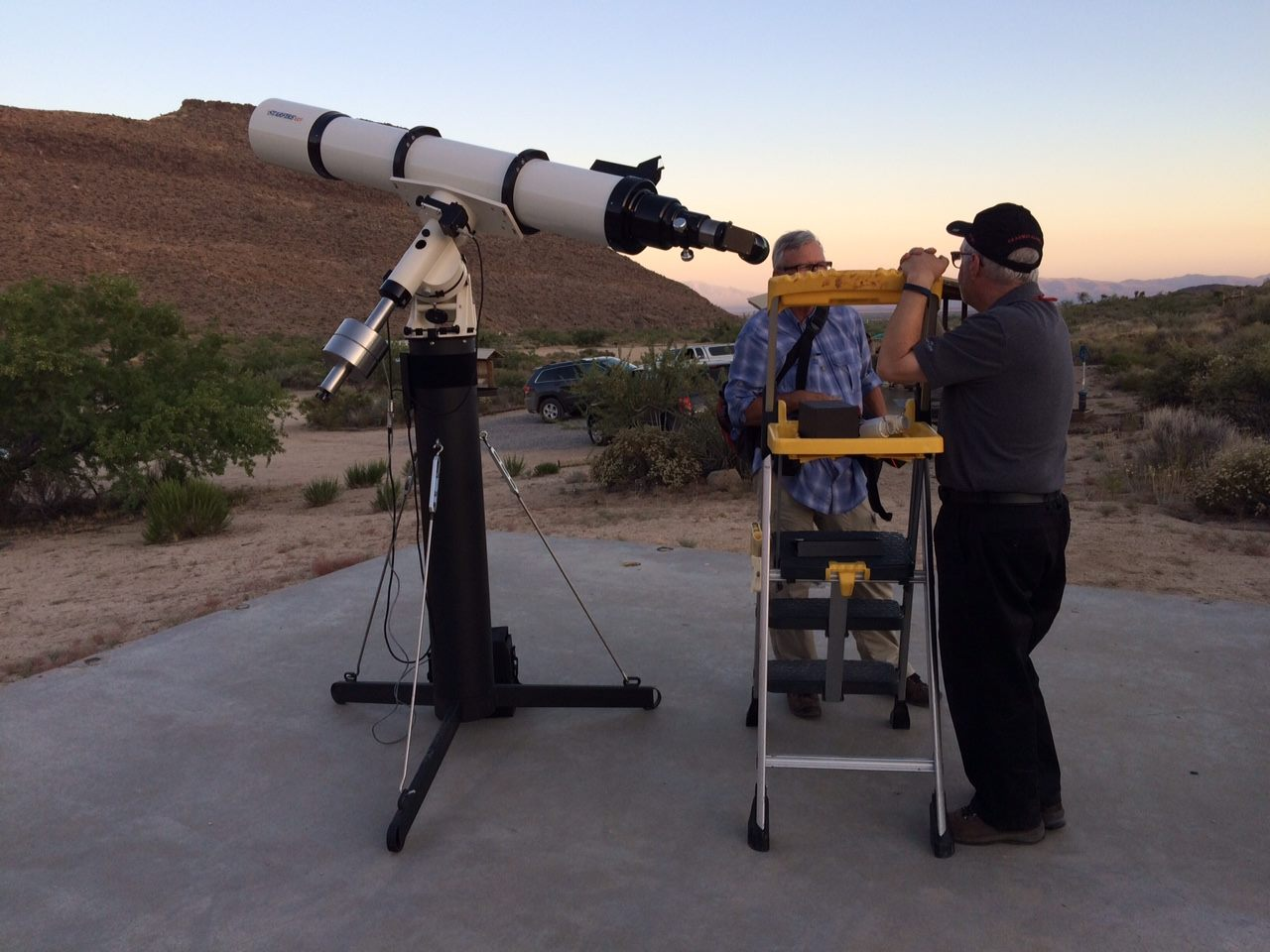 Astronomers setting up one of the telescopes and waiting for the setting sun to be replaced by millions of stars.
