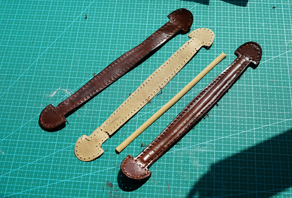 The piping core of the handle is hard plastic foam. Another 'leather-card paper-leather' construction.