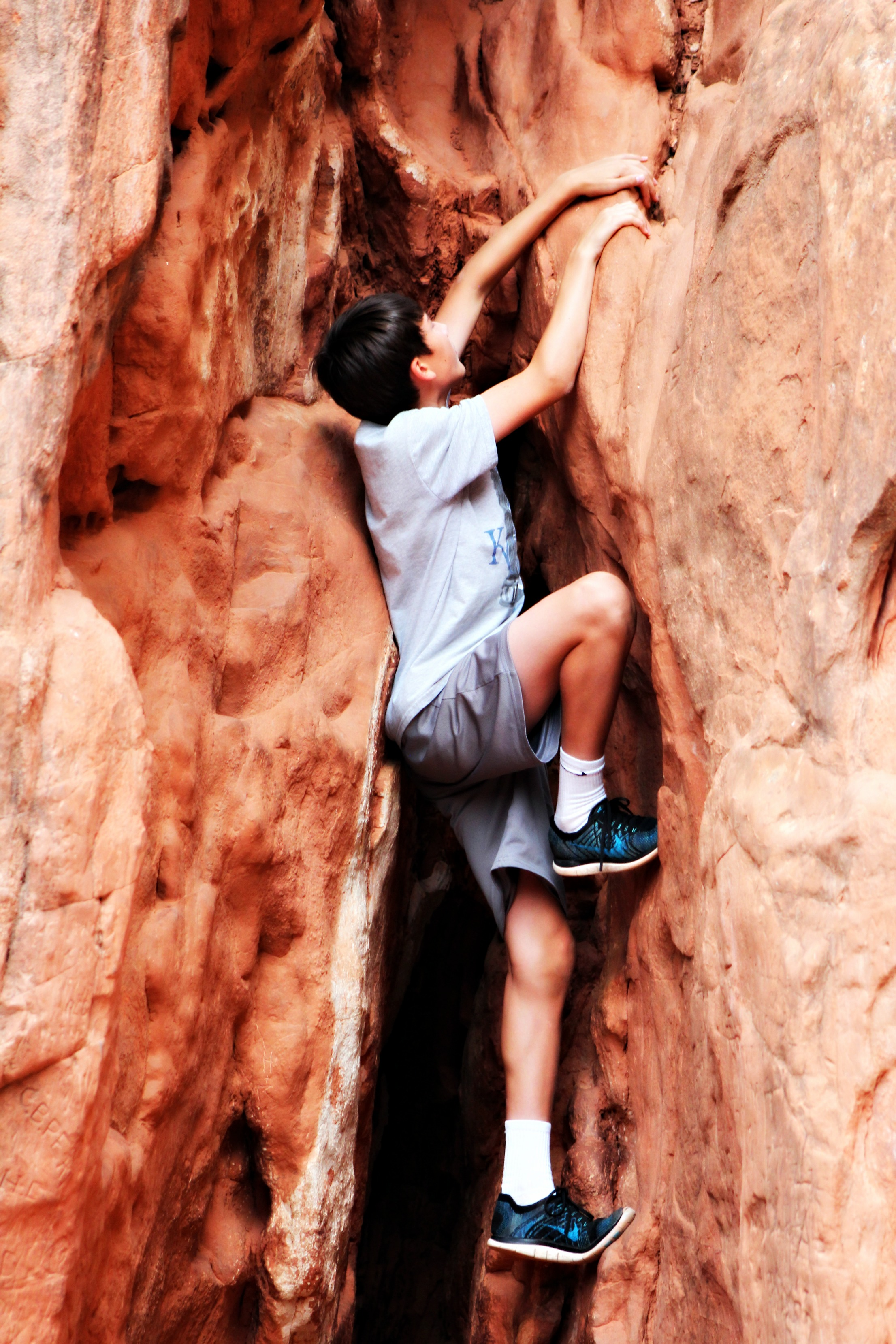 boy-climbing-red-rocks