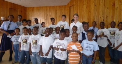 Ayla with school children after her presentation in the Bahamas.