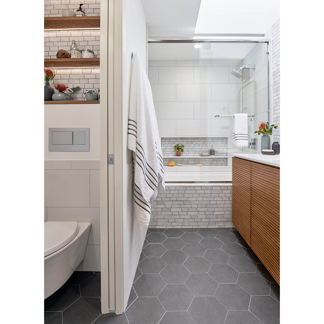 """The white/gray palette and geometric design is softened by warm, honey-toned custom cabinetry and shelving.  All """"After"""" photos courtesy of Dean J. Birinyi Photography."""