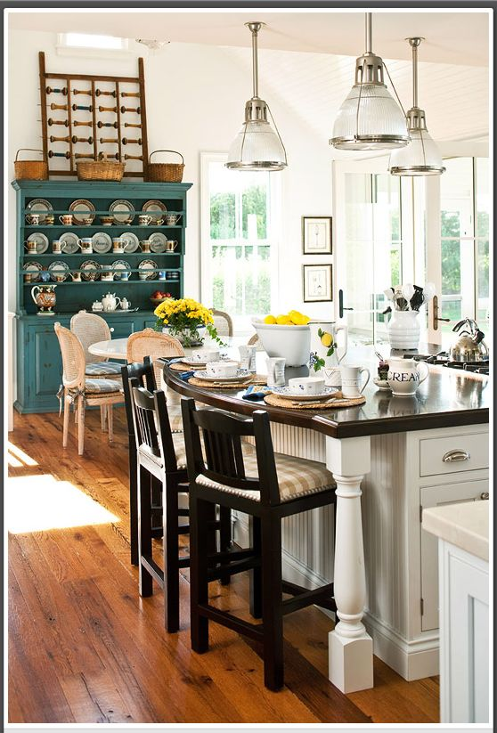 This is a vintage blue-painted cabinet with open shelves to store dinnerware that is right where you need it to set the table!!