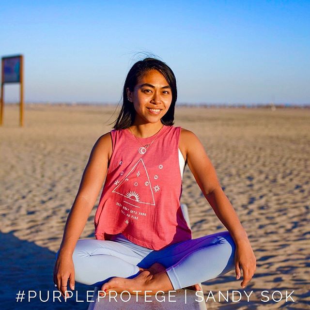"Long Beach say hello to Sandy Sok, your next #purpleprotege! A graduate of our recent #pyspring2019 class, she is an accountant that walks into the studio with positivity, confidence and swagger. ⠀ ⠀⠀⠀⠀⠀⠀⠀⠀ ""Once I'm there, I'm there. I don't think about anything else. It helps me step away from whatever is happening. I don't even bring my phone in. I leave it in my car. No devices. distractions…"" ⠀ ⠀⠀⠀⠀⠀⠀⠀⠀ No devices. No distractions? Geez, calm down Robert Frost. ⠀ ⠀⠀⠀⠀⠀⠀⠀⠀ ""Oh wait! I lied! I always have my watch on! But that's to help keep track of my workout. Hehe. Ok, I'm a poser. I'm not a fitness monk."" ⠀ ⠀⠀⠀⠀⠀⠀⠀⠀ A fitness monk she is not, but with a strong yoga practice and growing up in Long Beach and going to high school with the Dodgers Justin Turner, was she always so athletic? ⠀ ⠀⠀⠀⠀⠀⠀⠀⠀ ""I'm sorry, Justin who? I really don't know sports! I was really into the arts and drawing growing up. So much so that I failed P.E. because I kept going to art class instead! In fact, I never even worked out before I went to yoga LOL."" ⠀ ⠀⠀⠀⠀⠀⠀⠀⠀ So humor and humility is not lost with her. But how does she seem to be so comfortable in her own skin? ⠀ ⠀⠀⠀⠀⠀⠀⠀⠀ My parents were refugees. They didn't have time to sit and be depressed. They just survived and thrived and so I think that was probably the best example for me growing up. And so in terms of teaching and yoga, I don't want to come off as robotic or unnatural. I'm just, me. I just want to have fun. I really love yoga and I want to share what I love to others. So hopefully, since I'm myself, that will help others be comfortable with who they are as well. ⠀ ⠀⠀⠀⠀⠀⠀⠀⠀ Practice with Sandy for just $5 at 1pm on Wednesdays for the next few weeks."