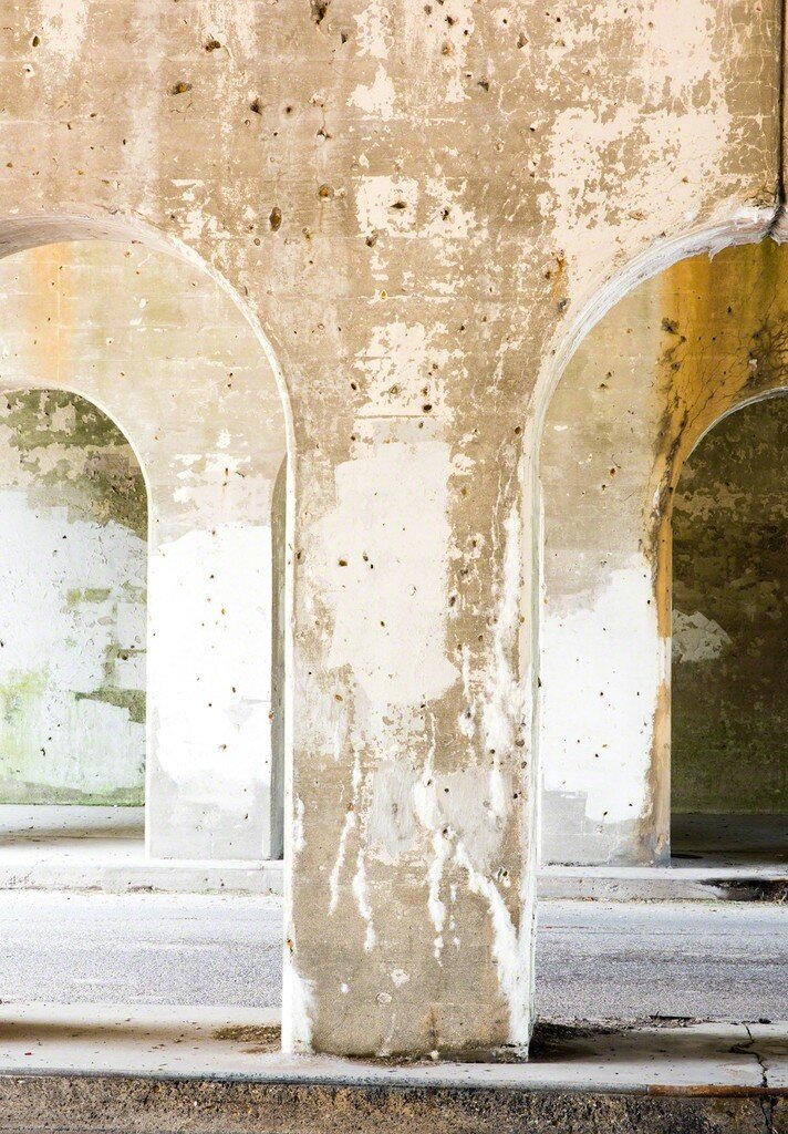 Strong light on masonry arches reveals a stain that suggests an abstract angel