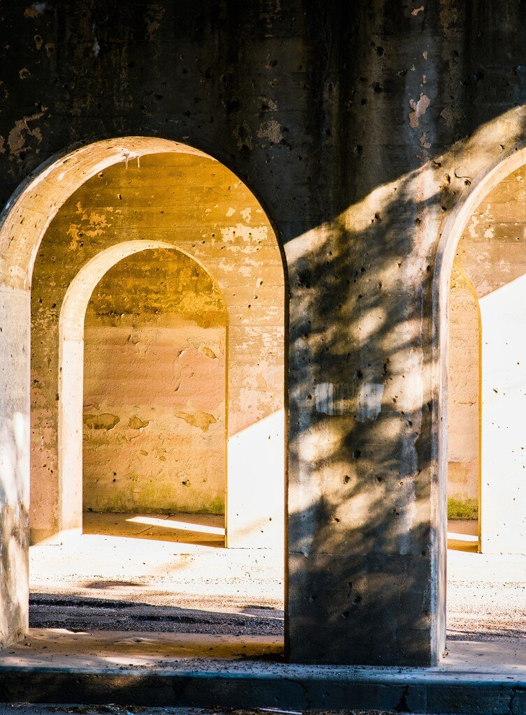 Orange light filters through a series of increasingly dark arches