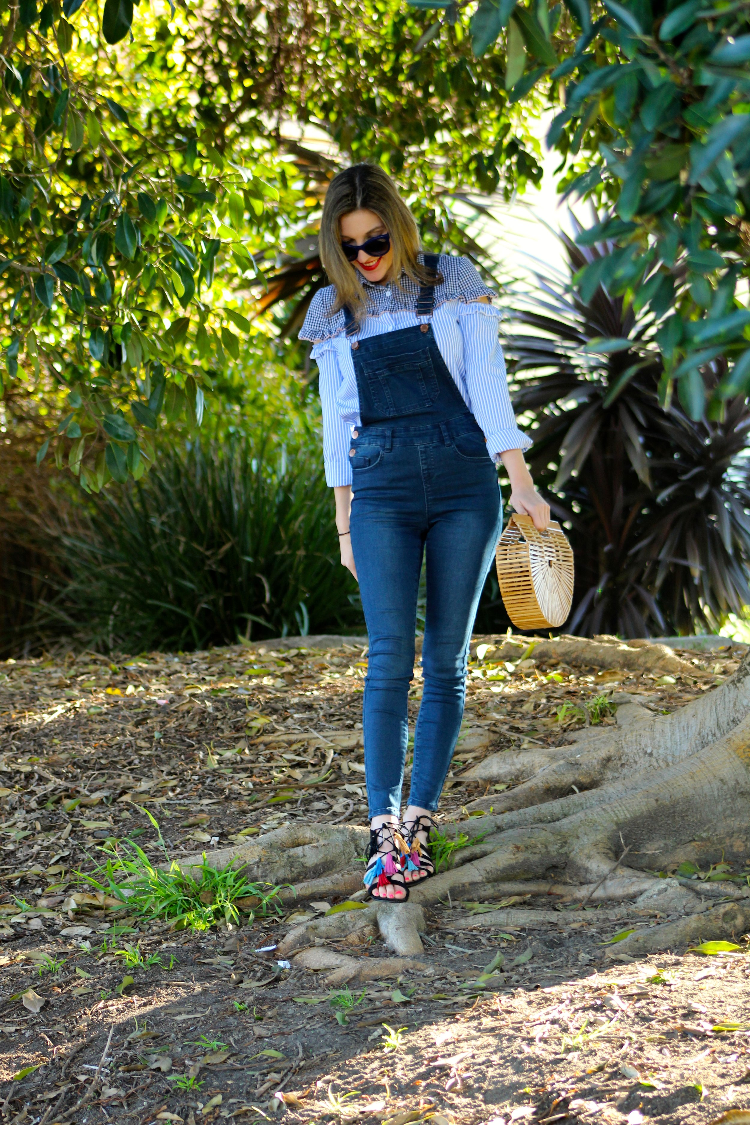 Top :  Shein  //  Overalls : Asos,  similar here  //  Shoes : Forever 21,  similar here //  Bag :  Cult Gaia  //  Sunglasses :  Chanel    Yay! It's Friday! I am excited to share this post with you guys today! I have been talking a lot about   Shein.com   recently but only because I have been finding soooo many goodies on their site! This gingham top is so unique, I love it! The detail cutouts, the different patterns and the ruffles are just so one of a kind. This shirt definitely has a lot going on so I wanted to pair it with something more toned down and simple. I love overalls! I have talked about them time and time again on the blog. They are just so easy peasy- but so on trend! If you love unique stand out tops like me, I have linked a few more of my picks  here ,  here , and  here . I wanted to keep the fun going with this outfit, so I added some colorful fringed sandals and my favorite bamboo clutch! Make sure you guys head to   Shein.com     to find a variety of fashionable items that you are sure to turn heads in! Happy Shopping!  Have a lovely weekend friends!  ~ Nicole   Thank you to Shein.com for sponsoring this post.