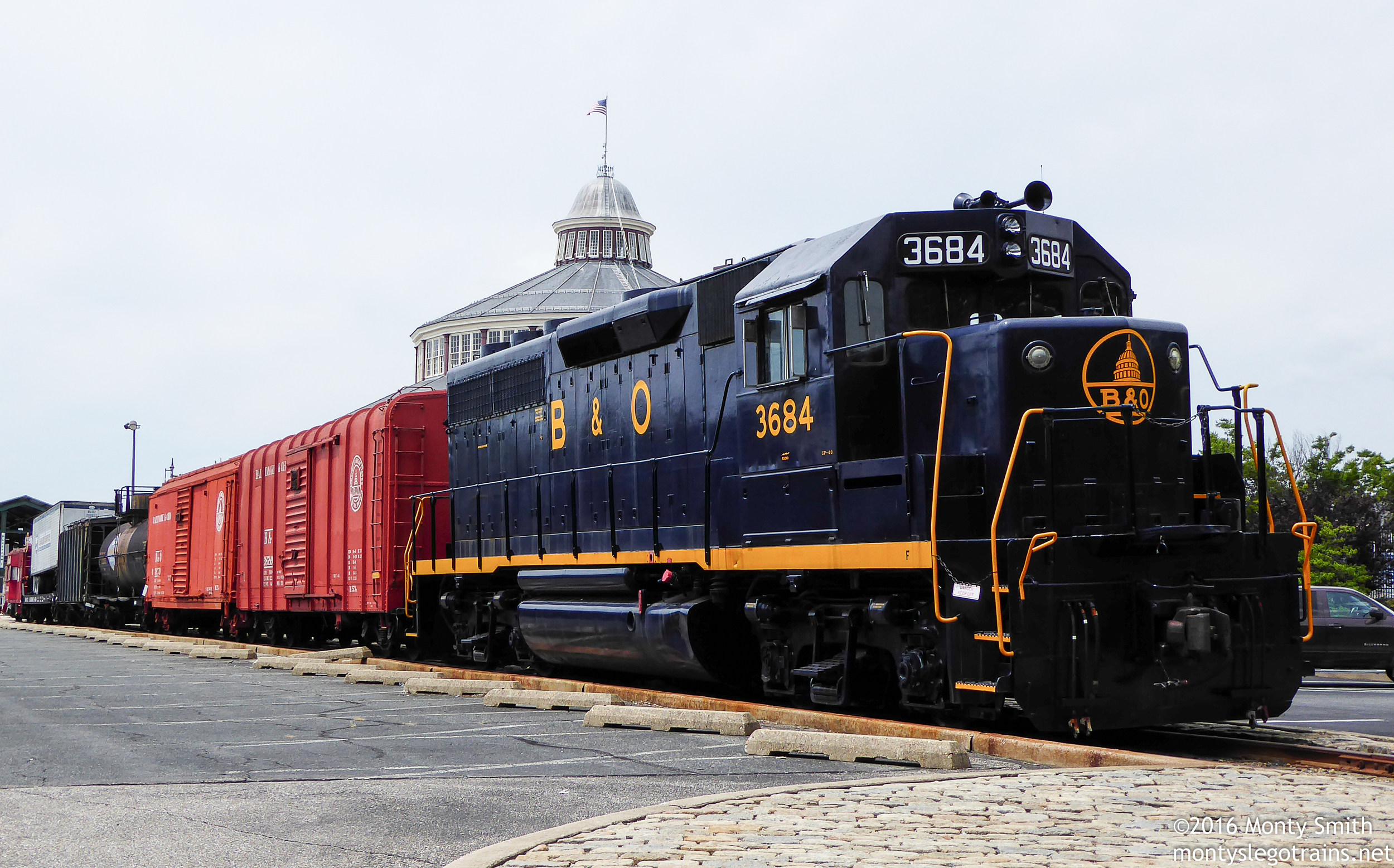 A Baltimore & Ohio geep on display out front at the B&O Railroad Museum, with the museum's trademark clerestory roof in the background.