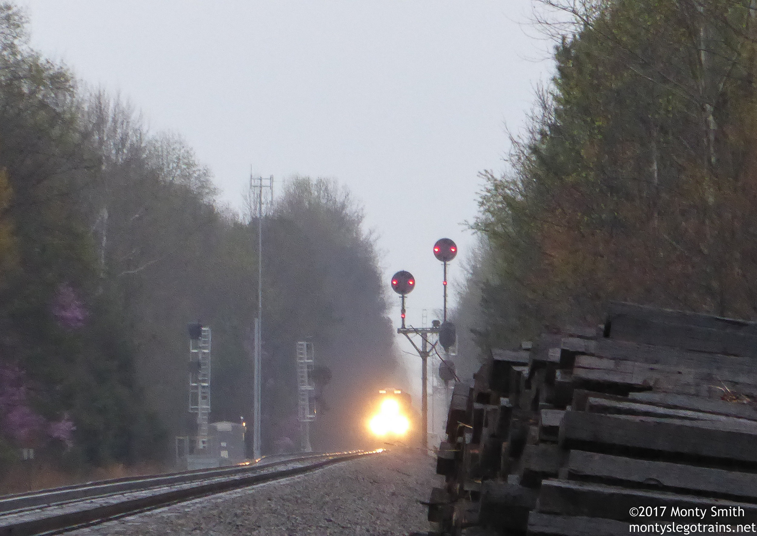 The circus train approaches through increasingly heavy rain, framed by soon-to-fall N&W CPL signals. Their replacements can be seen with signal heads turned 90 degrees. They will face the correct directions when placed into service.