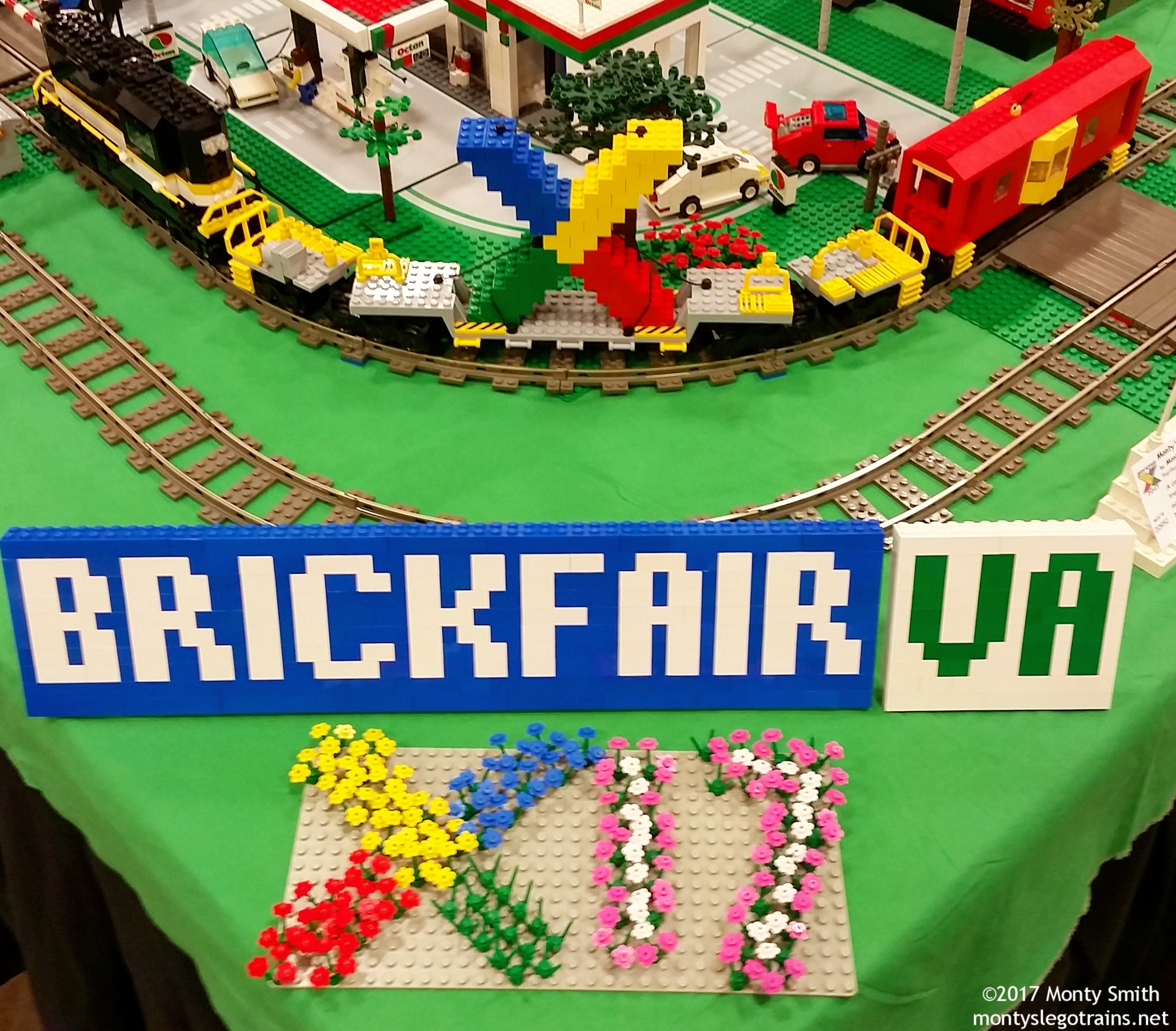 """The theme for this year's BrickFair was """"X"""" or """"10,"""" for the 10th anniversary of the event. Fittingly, I built a 10-axle flatcar carrying a large """"X"""" in the BrickFair color scheme, shown here with my BrickFair VA sign."""