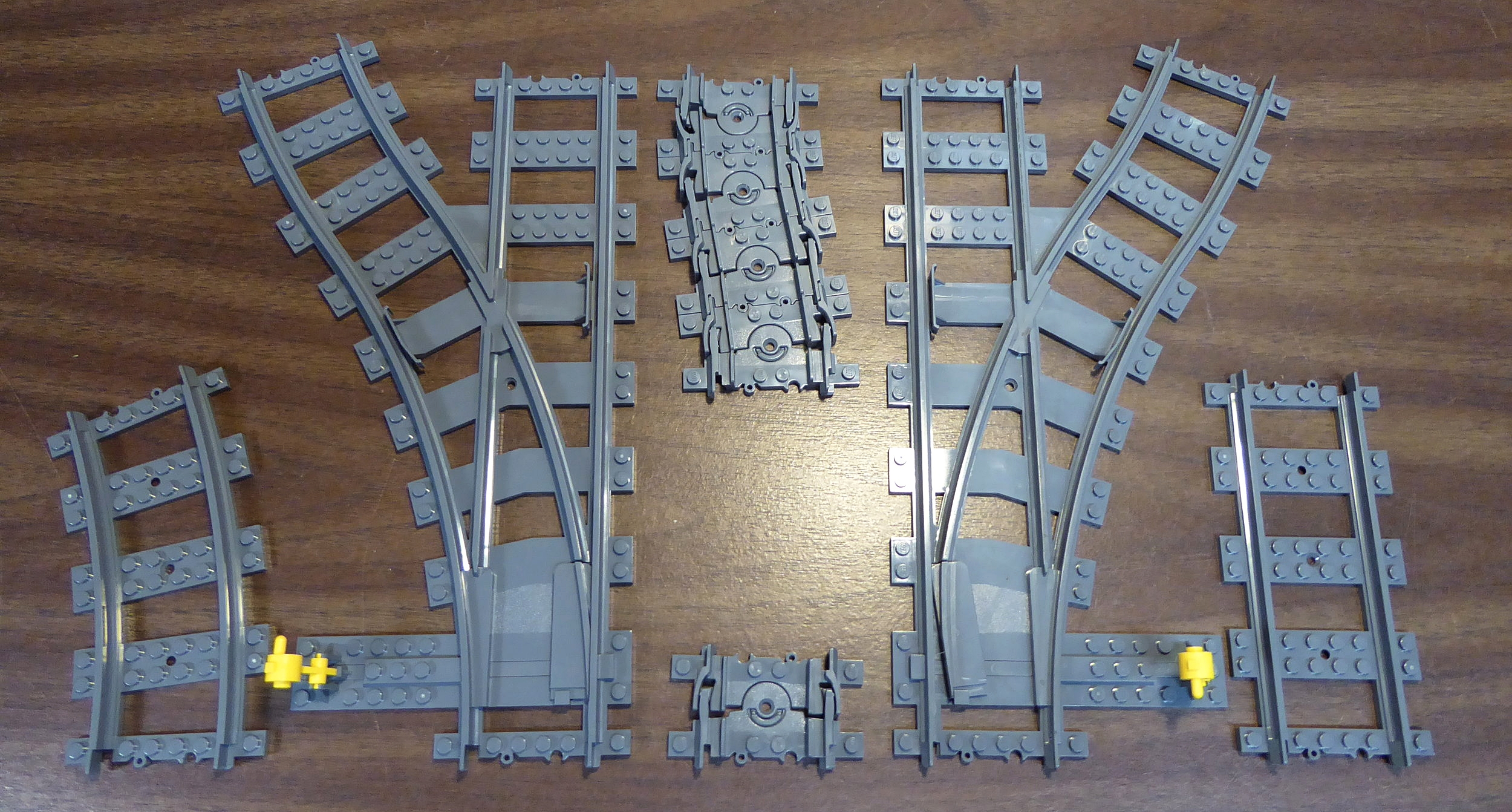 This photograph shows the whole range of official Lego train track parts. On the far left is a standard curve, and on the far right is a standard straight. The bottom center shows one piece of flexible track, and the top center shows four pieces of flexible track connected together, equaling the length of the curve and straight track, but with the ability to shift into unusual shapes. Also shown is one left-hand switch (set for the diverging route) and one right-hand switch (set for the straight route).